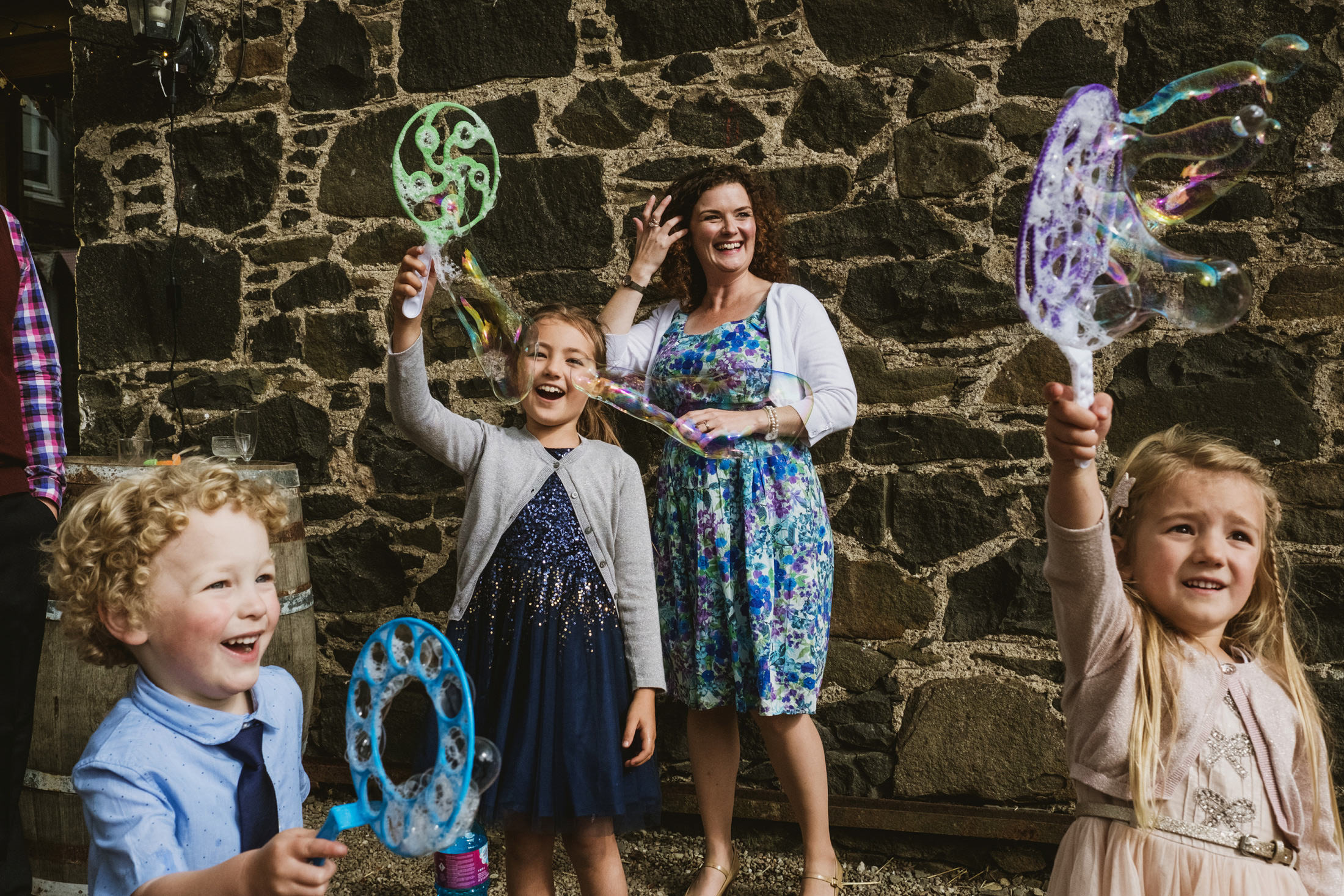 Wedding guests, old and young alike playing with bubbles