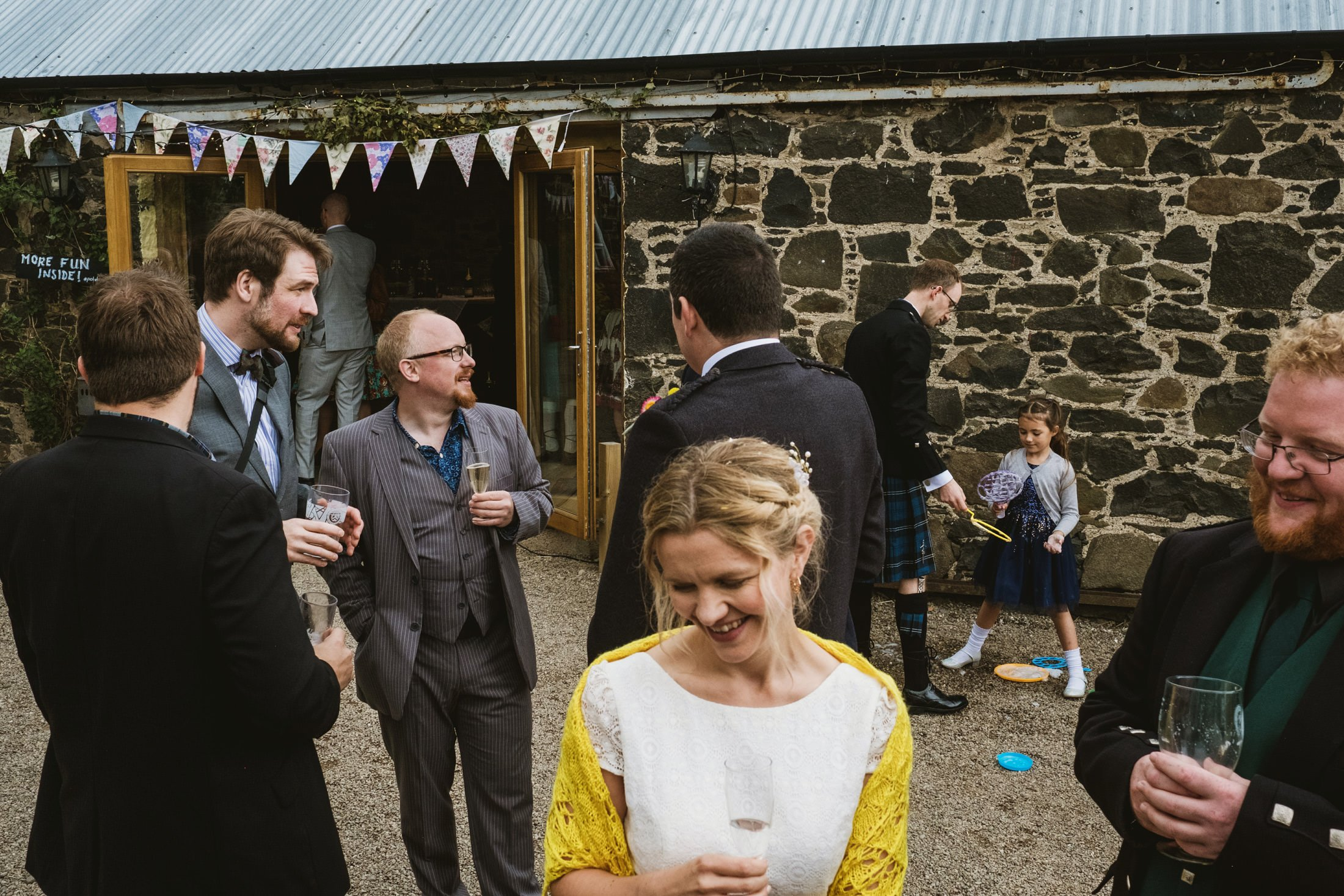 Comrie Croft Wedding Photography. Bride in the centre of the frame surrounded by guests at her wedding reception at Comrie Croft