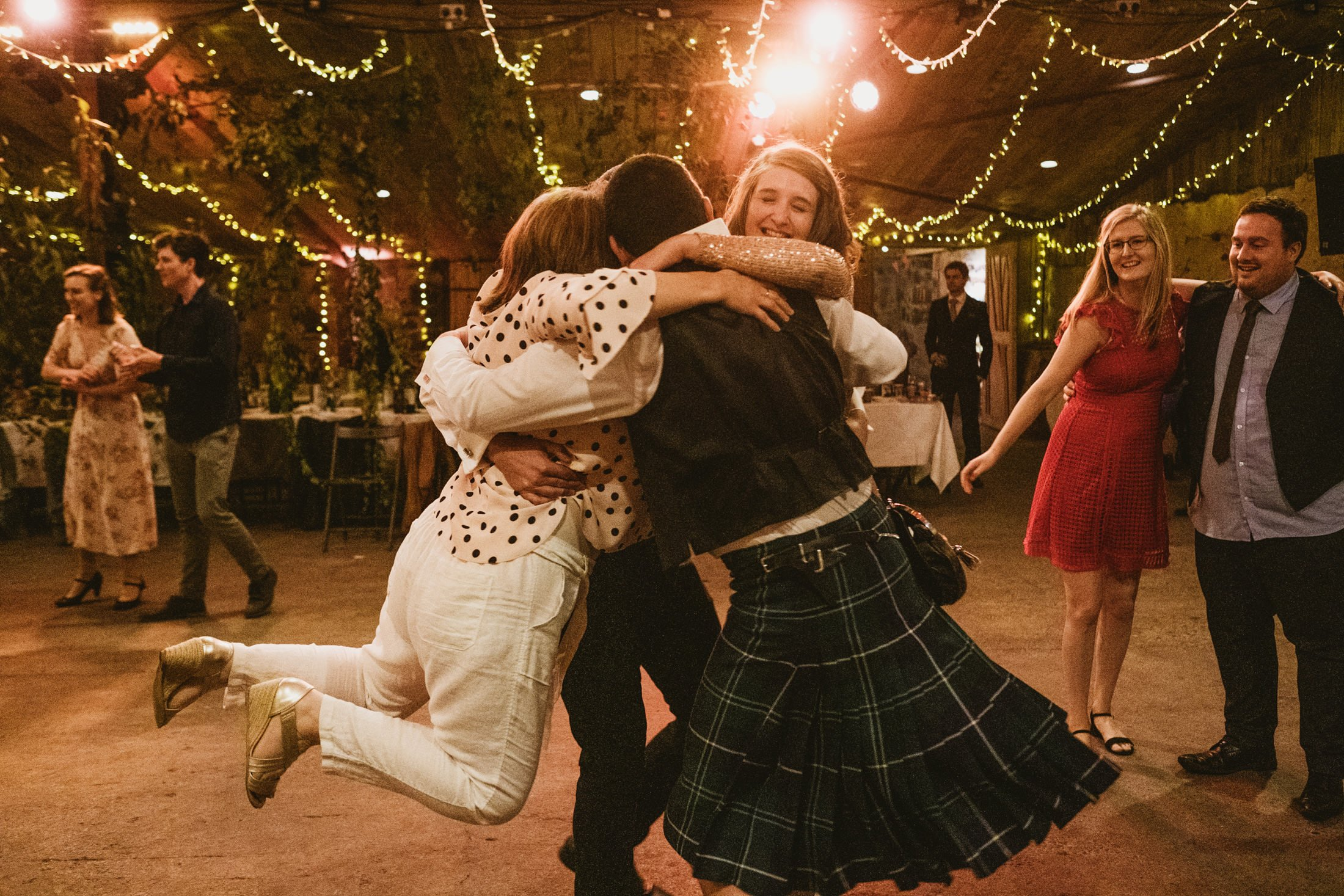 bride, groom and all their friends dancing in a circle