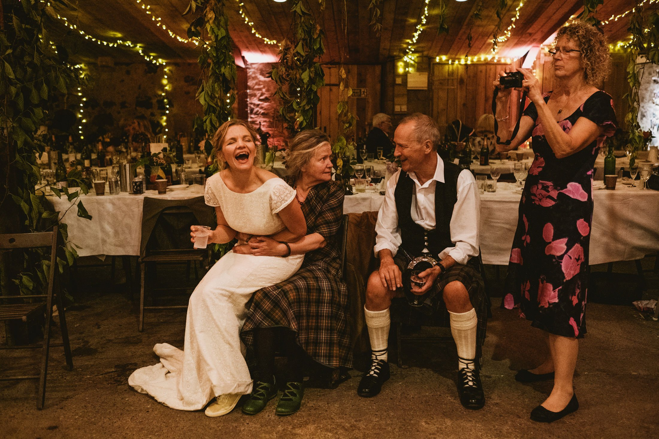 bride sitting on a knee laughing with guests