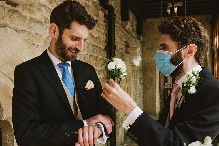 Covid Secure intimate wedding scene. A groom checks the time on his wristwatch whilst a groomsman in blue medical mask holds out the groom's buttonhole ready for fitting