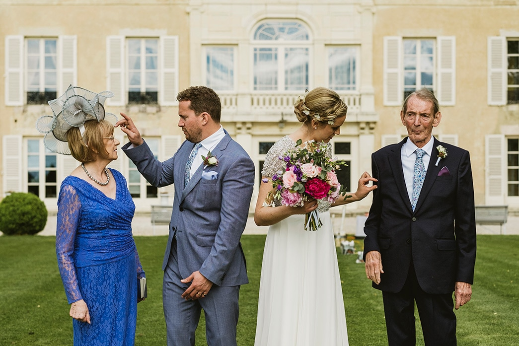 documentary style wedding photograph of bride and groom tidying the outfits of the father of the bride and mother of the bride whilst standing in front of a French Chateau