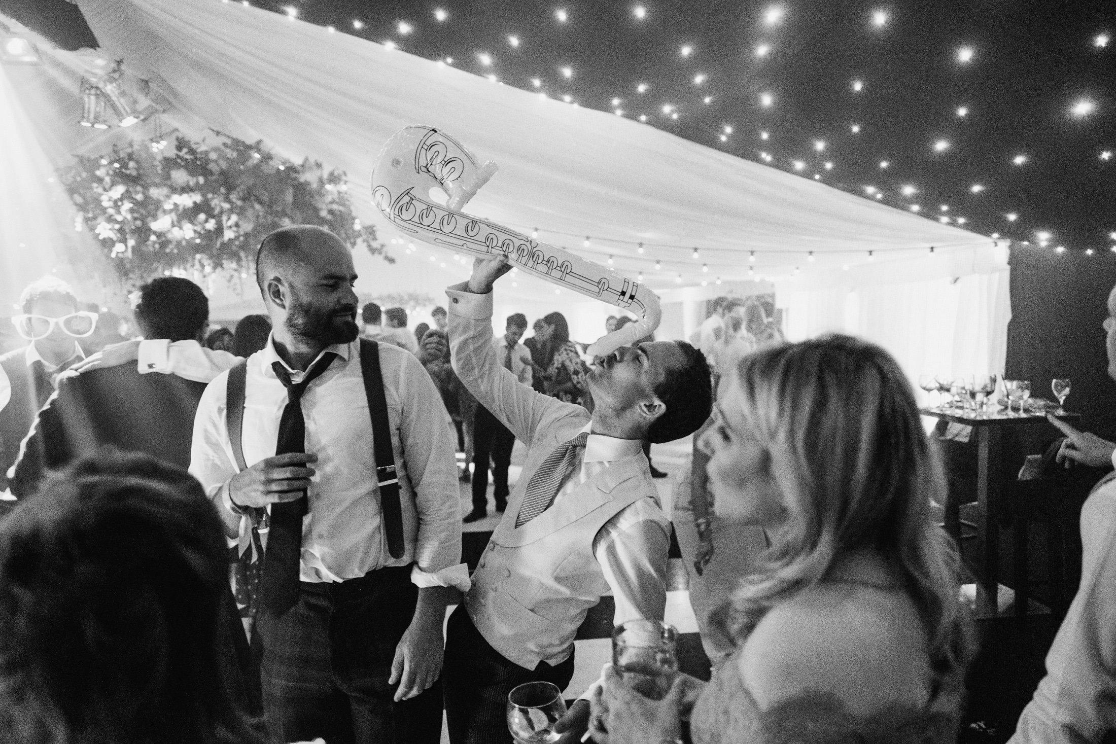 wedding guest on dance floor with blow up instruments