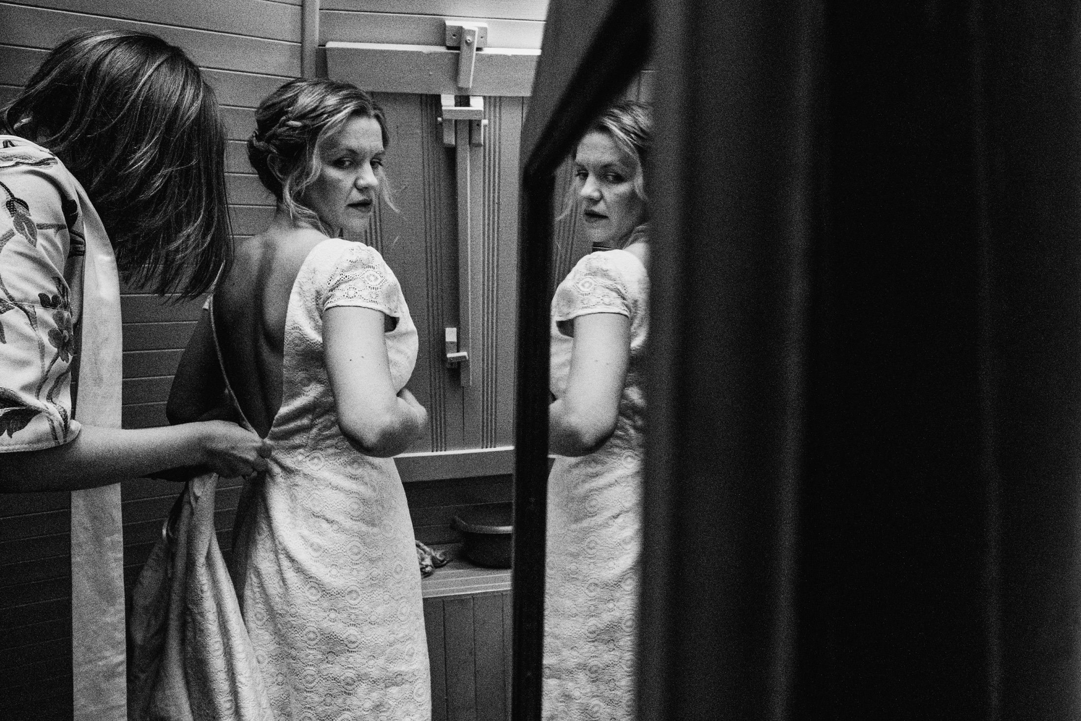 bride getting ready into her dress, reflection in the mirror