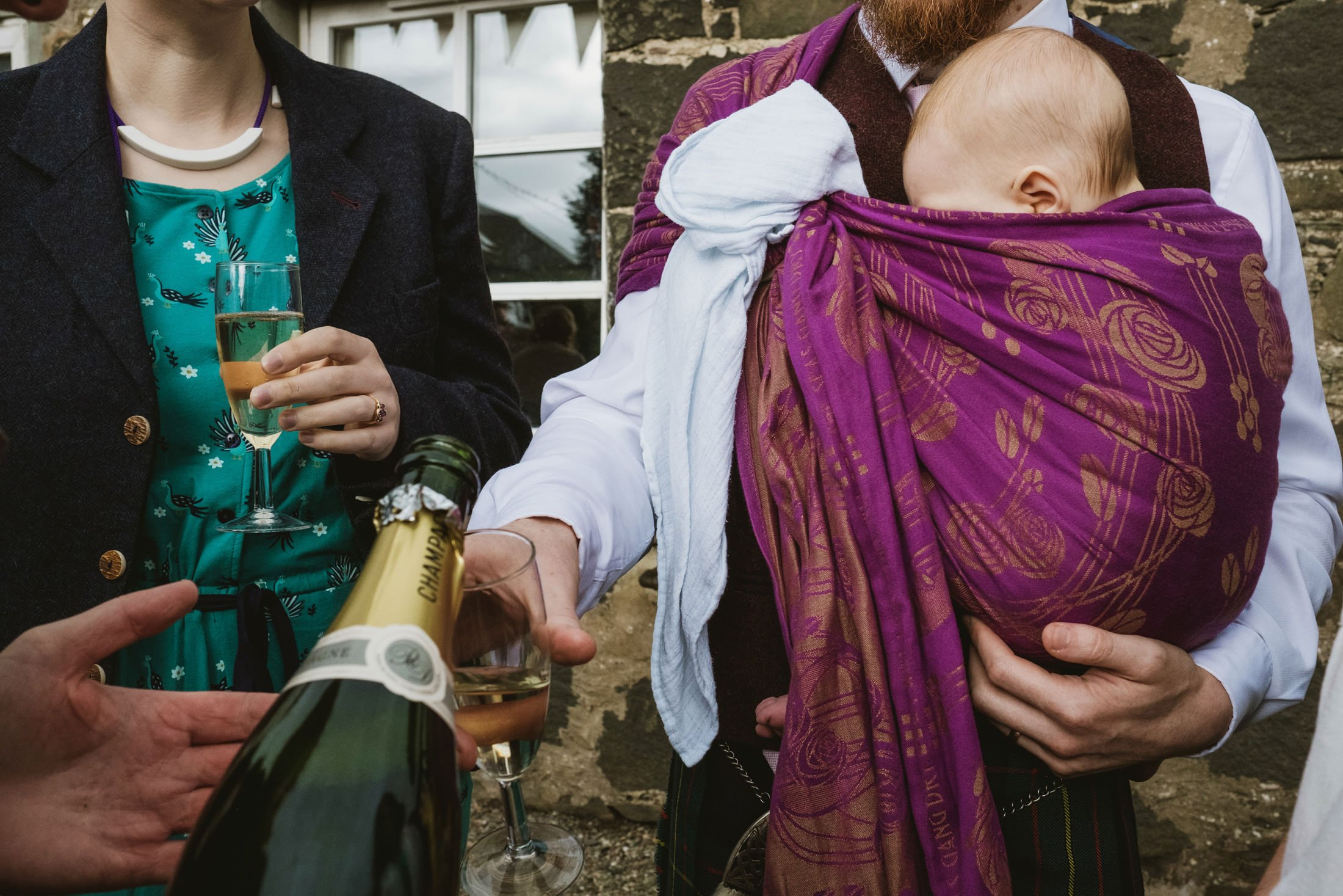 Intimate reportage wedding photograph of guests at Comrie Croft wedding. Photograph of baby in sling as guests are served champagne