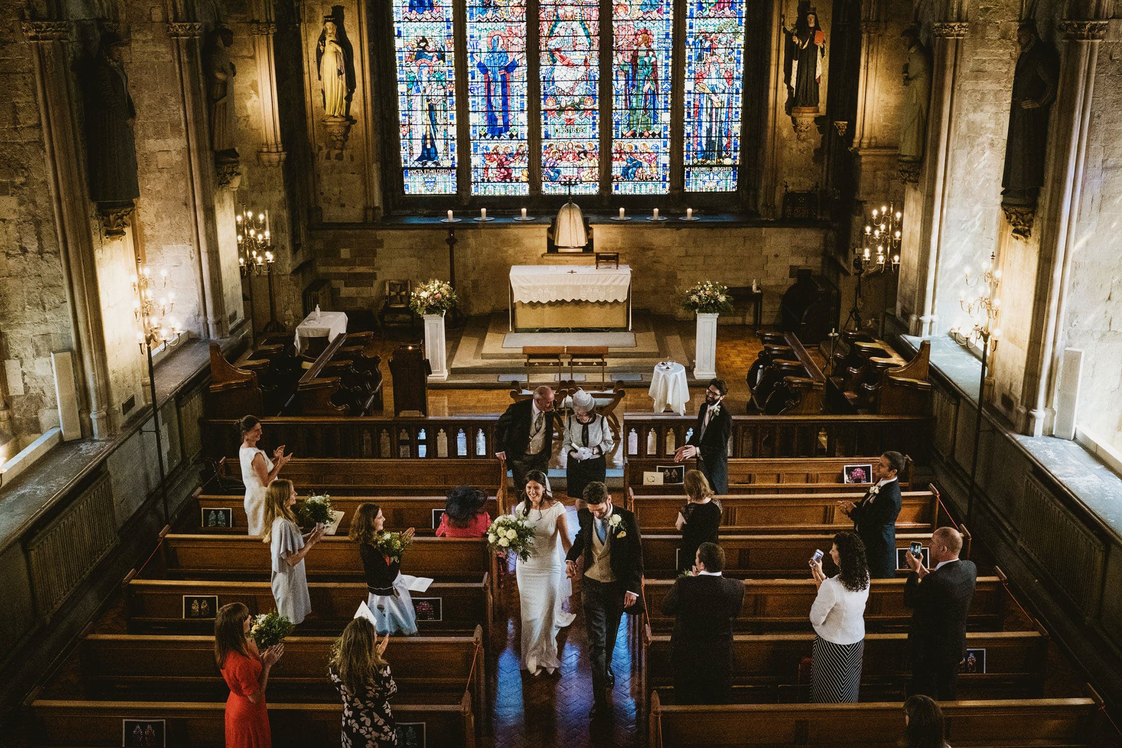 Bride and groom walk back down the aisle as husband and wife as their guests applaud. Documentary wedding image photographed from church balcony