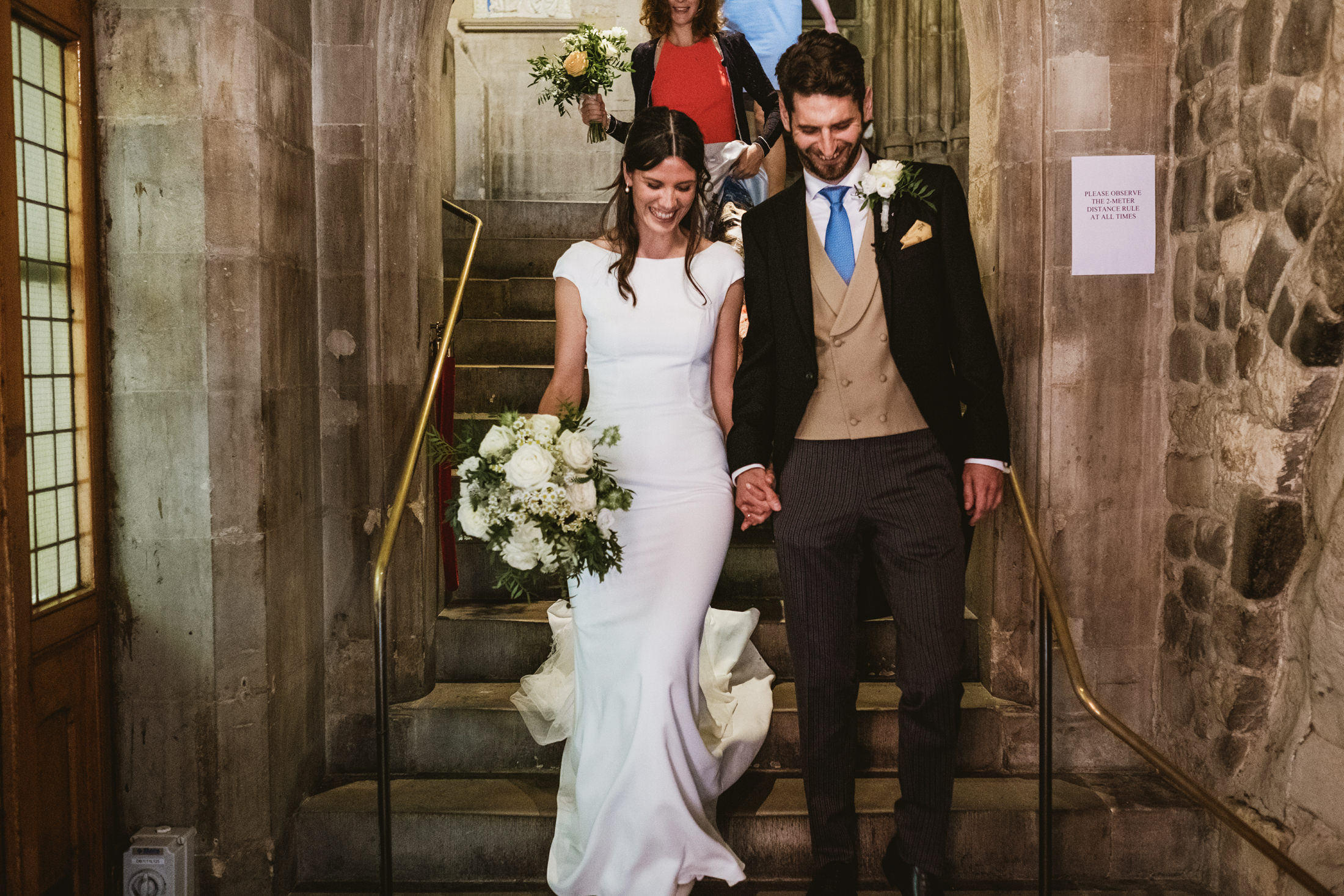 Bride and Groom walk down church steps hand-in-hand immediately following their wedding ceremony
