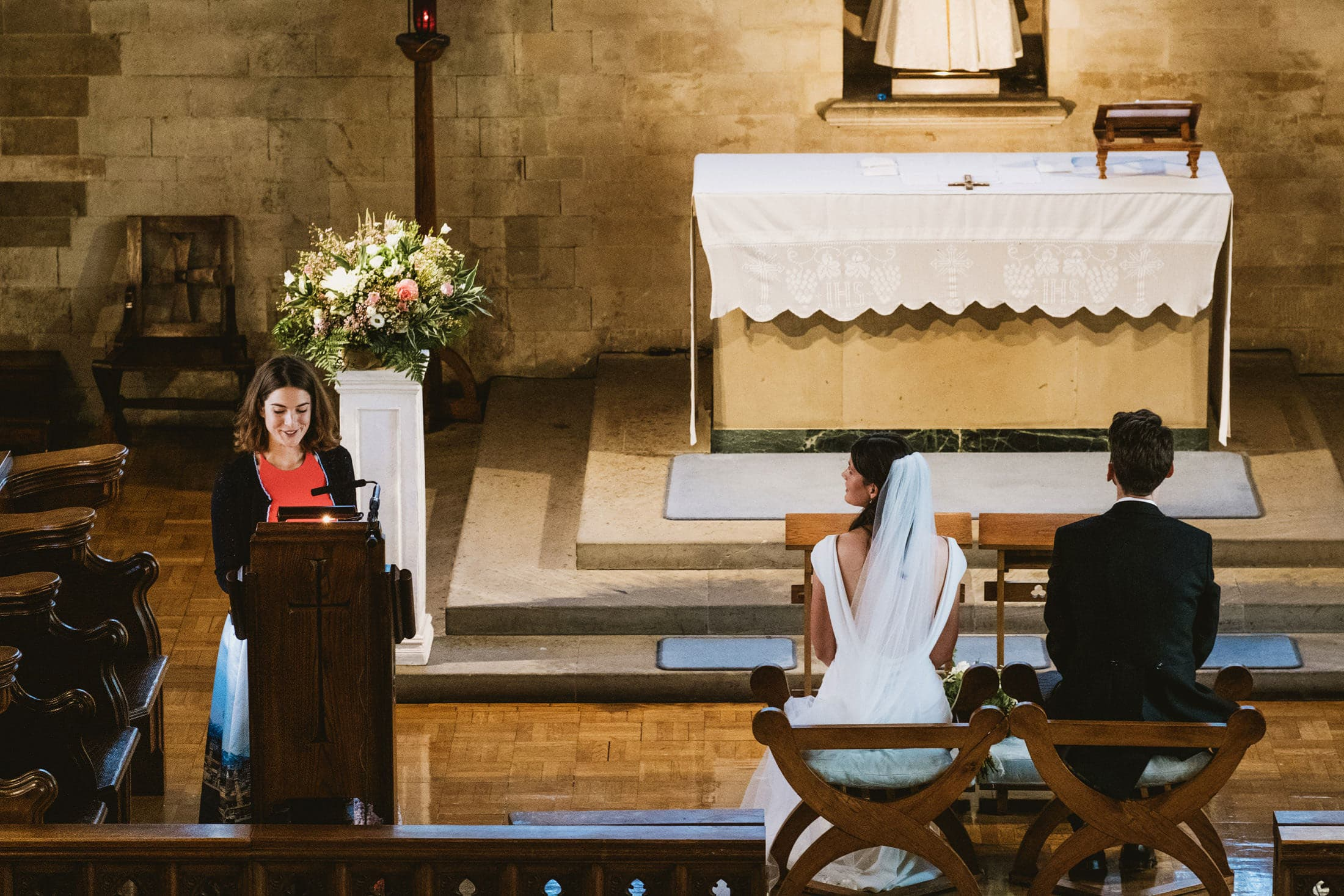 A wedding reading is delivered from a church lectern whilst the seated bride and groom watch on. Photograph captured from elevated plane on balcony.