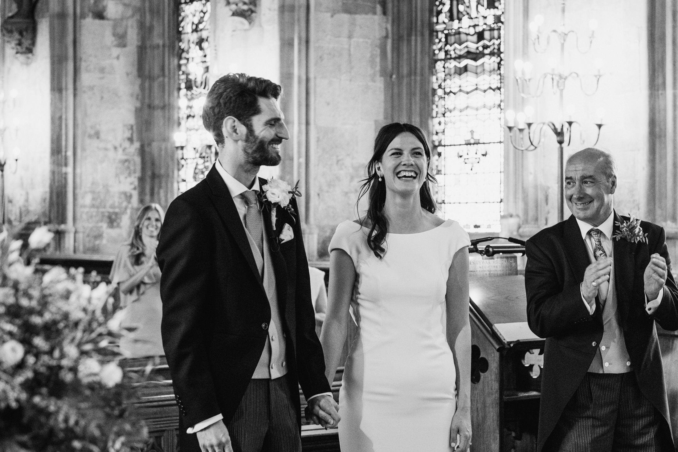 Smiling bride and groom are applauded by their socially distanced wedding guests at a London micro wedding ceremony