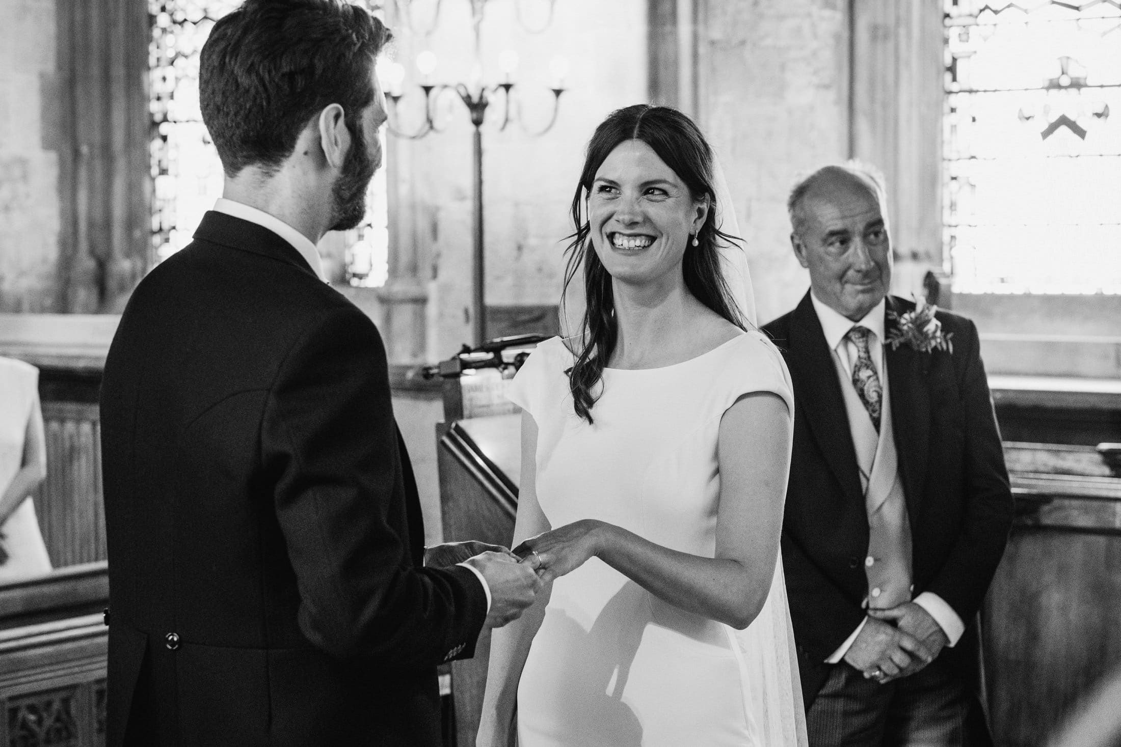 Bride and groom exchange rings and promises at an intimate London wedding ceremony. Black & white documentary style photography.