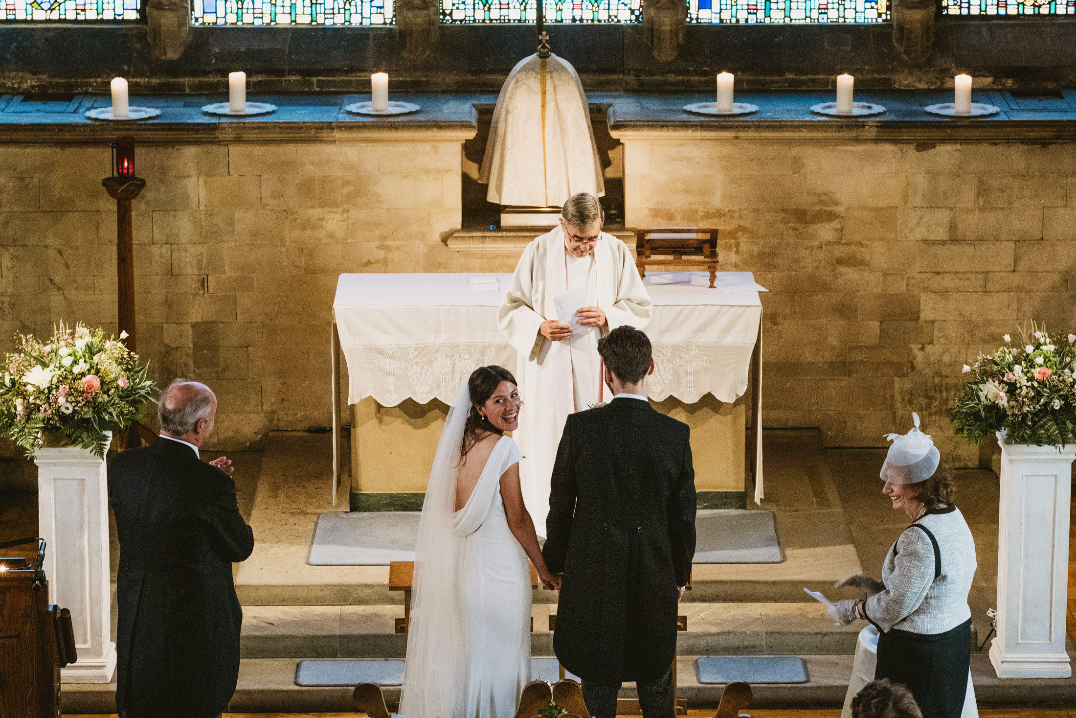 Bride smiles back towards her guest whilst standing with her groom and witnesses at the altar of St Ethelreda's RC Church, London during an intimate wedding ceremony. Documentary photograph captured from church balcony