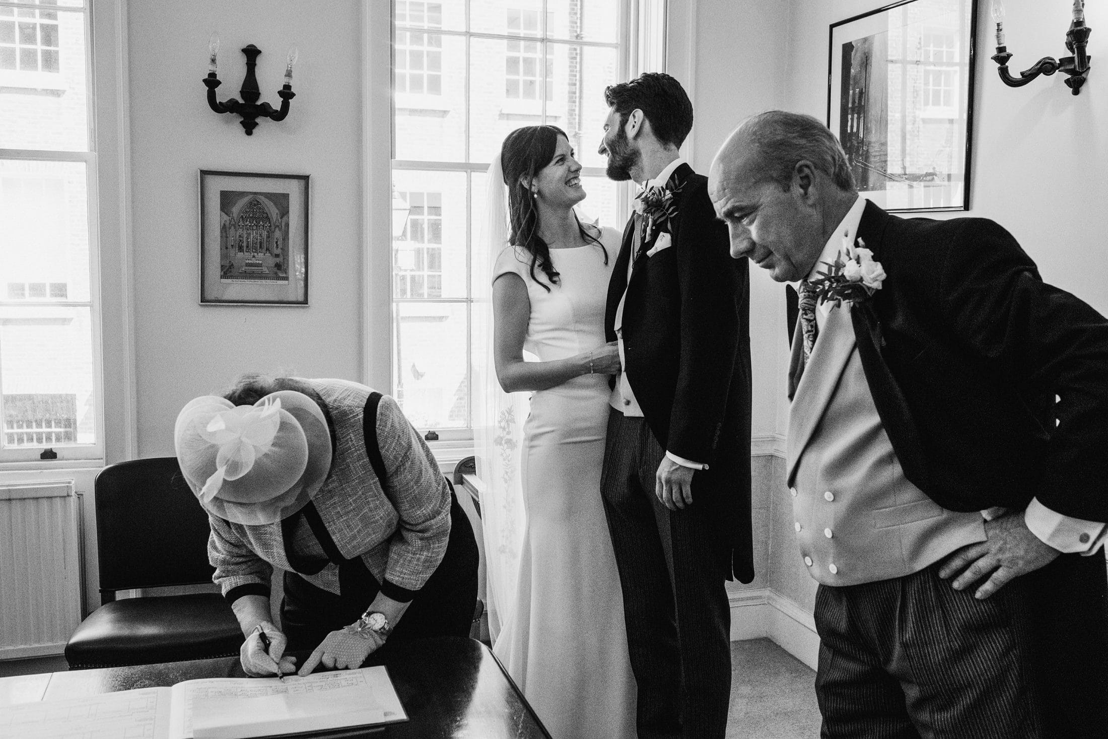 Woman leans down to sign the register at an intimate micro wedding. Beside her the bride and groom share a smile whilst in the foreground the father of the bride stands looking across the frame