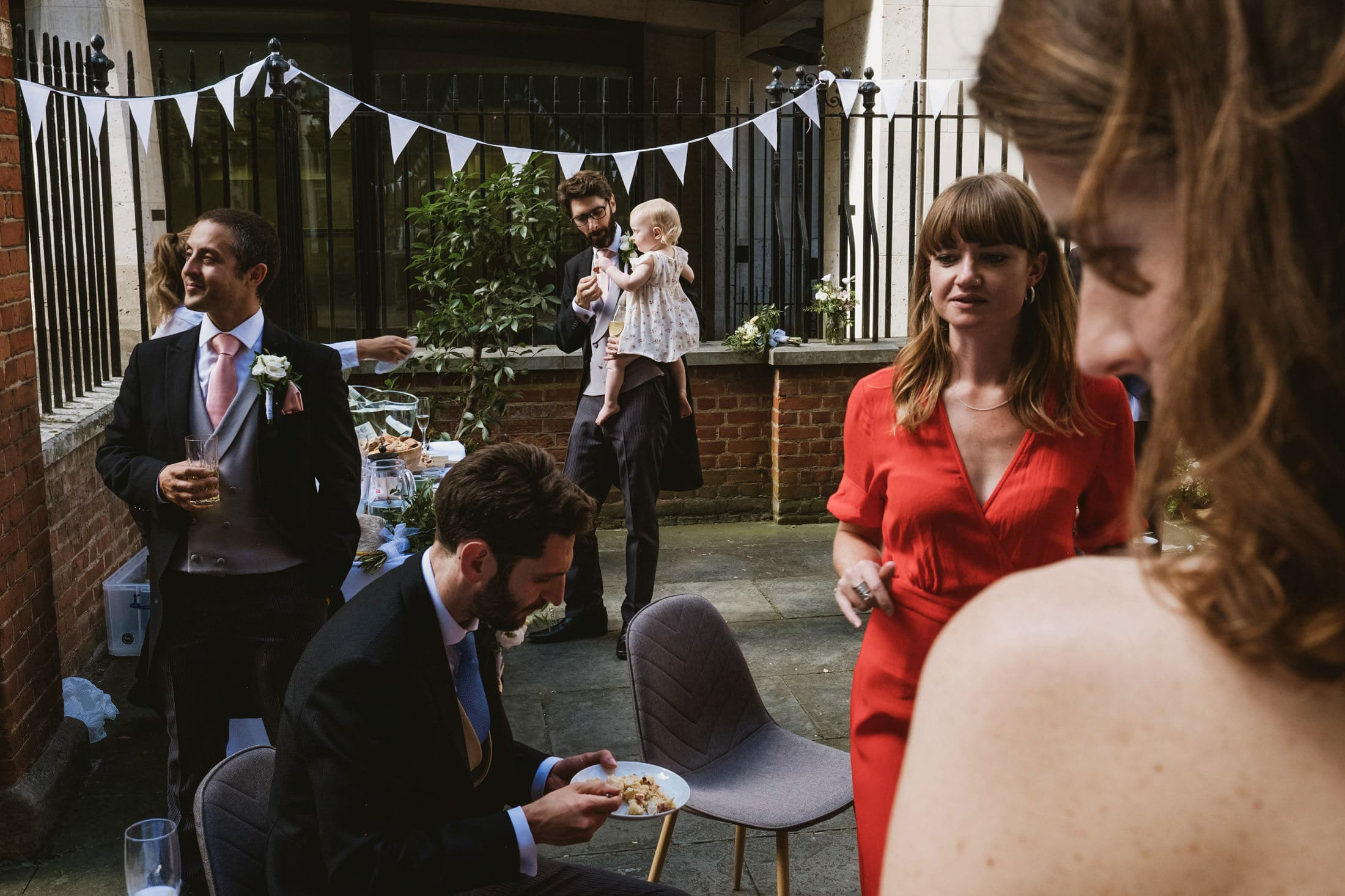 Wedding guests stand together in a London courtyard, all engaged in separate stories in this multi-layered image.