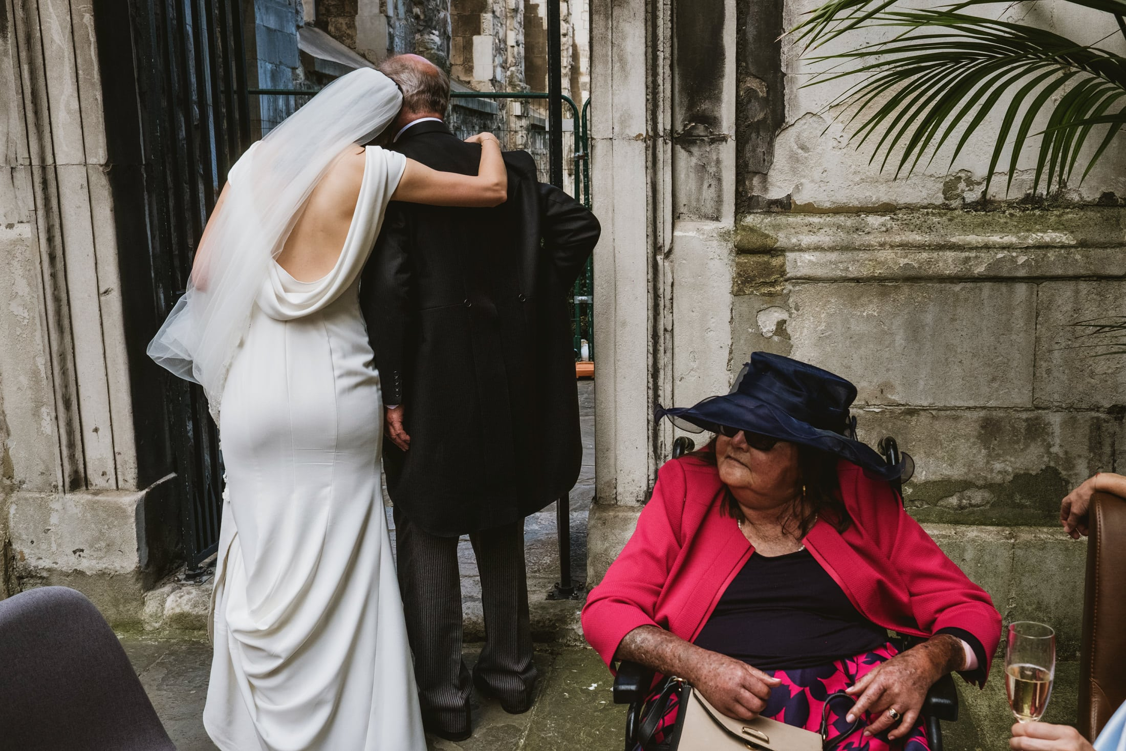 A bride places her head on the shoulder of her father standing beside her, both with their backs to camera. On the right of the frame is a woman seated in a wheelchair wearing a wide brimmed hat and sunglasses