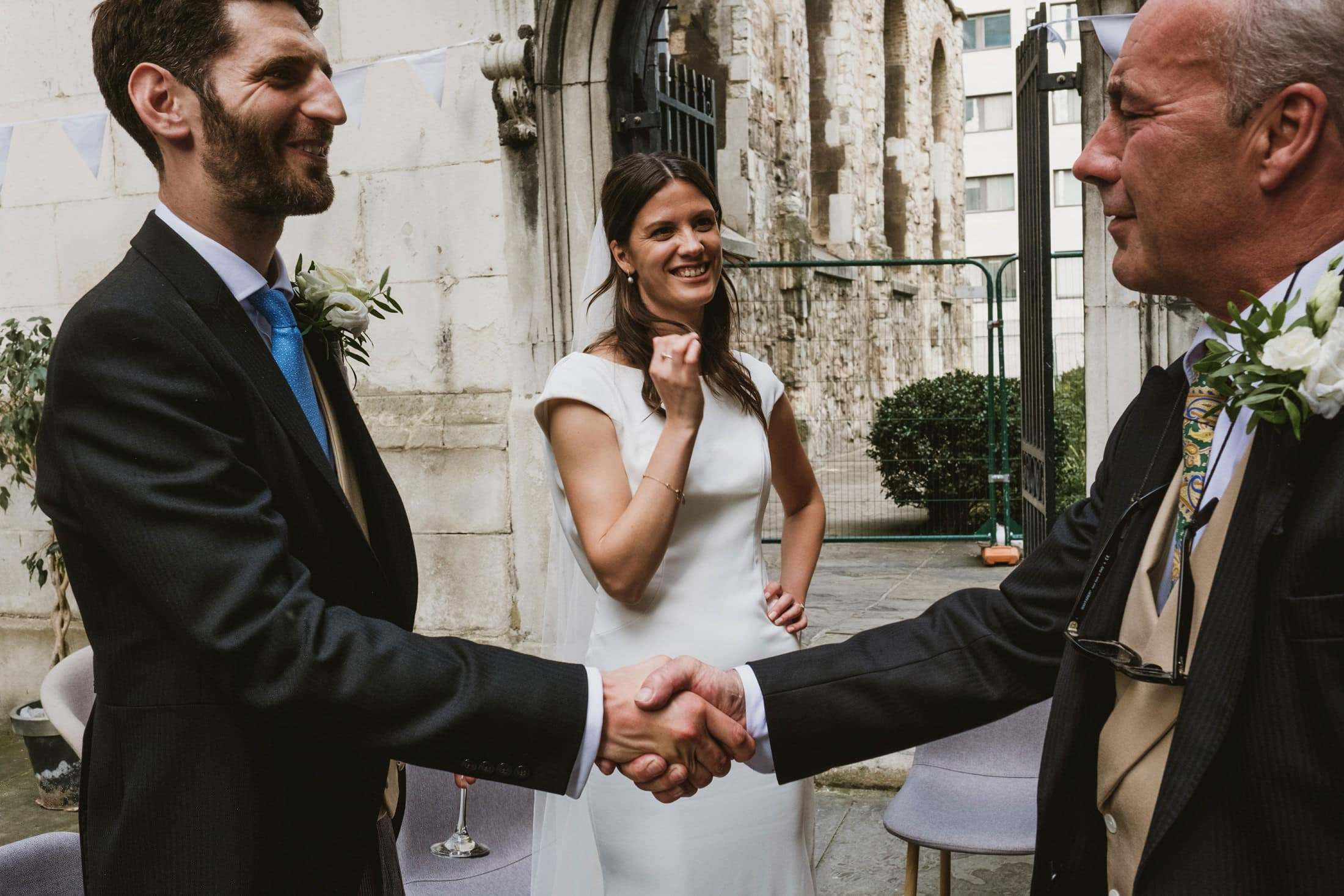 A groom and Father of the bride shake hands at an outdoor intimate wedding in London. Behind and between stands the bride watching on.