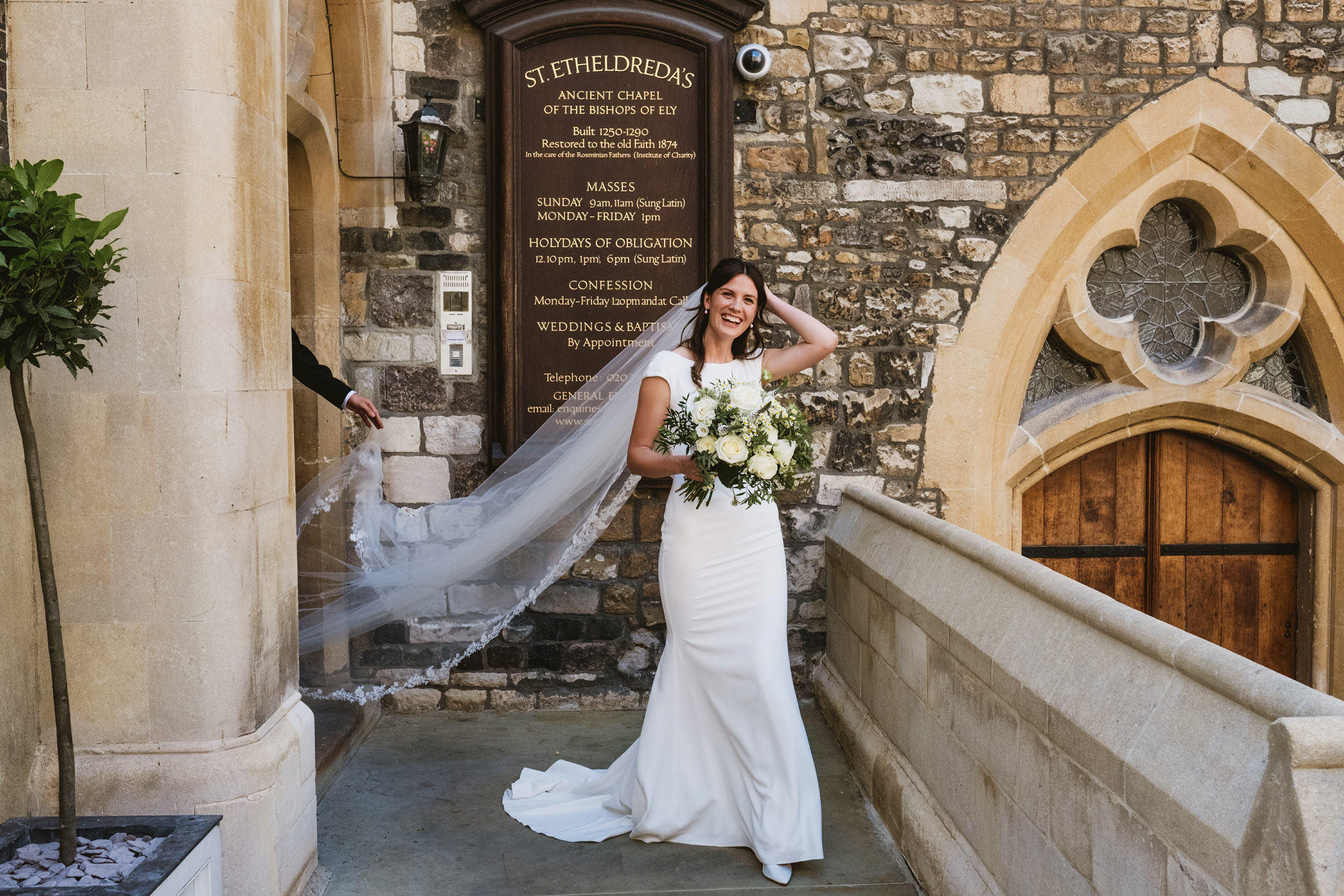 Smiling bride emerges from a London church. Holding the end of her veil is the arm of an unseen figure through the doorway.