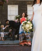 Documentary wedding photograph from an intimate wedding in London. In the foreground to the right of the frame a bride in white dress holds her wedding train, her veil floating out behind her, her face not included in the frame. In her right hand is her bridal bouquet, behind which a smiling bridesmaid holds another bouquet. Behind and to her right the groom bends down to take the hand of a young boy, a pram with another child framed between them. Far left of the frame a woman in a blue dress looks on.