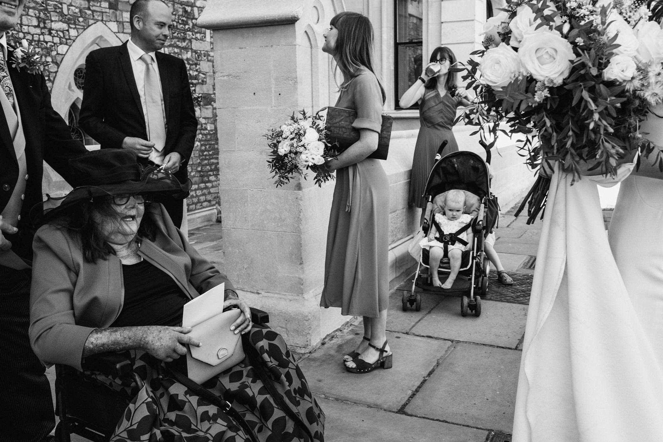 Black & White documentary wedding photograph at a London micro wedding. (Right) we can see the bridal bouquet, being held by the bride off frame. In the background a young child in a pram looks toward the camera, a third leg mysteriously coming from behind the pram whilst the children's mother takes a drink behind them. (Centre) a bridesmaid looks back towards the church entrance. Left a woman in a wheelchair provides symmetry with the pram, flaked by groomsmen.