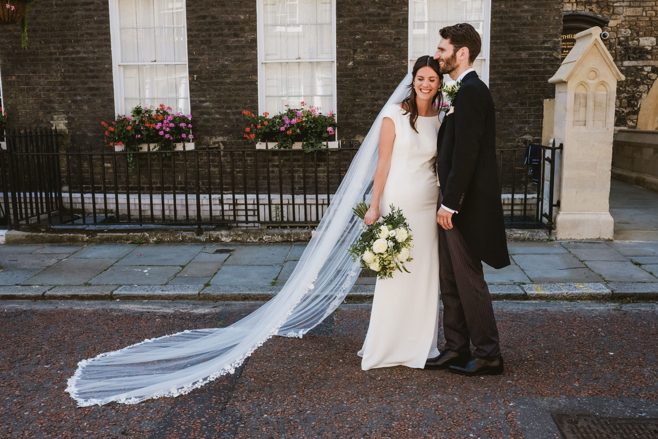 A bride and groom stand together on a London street