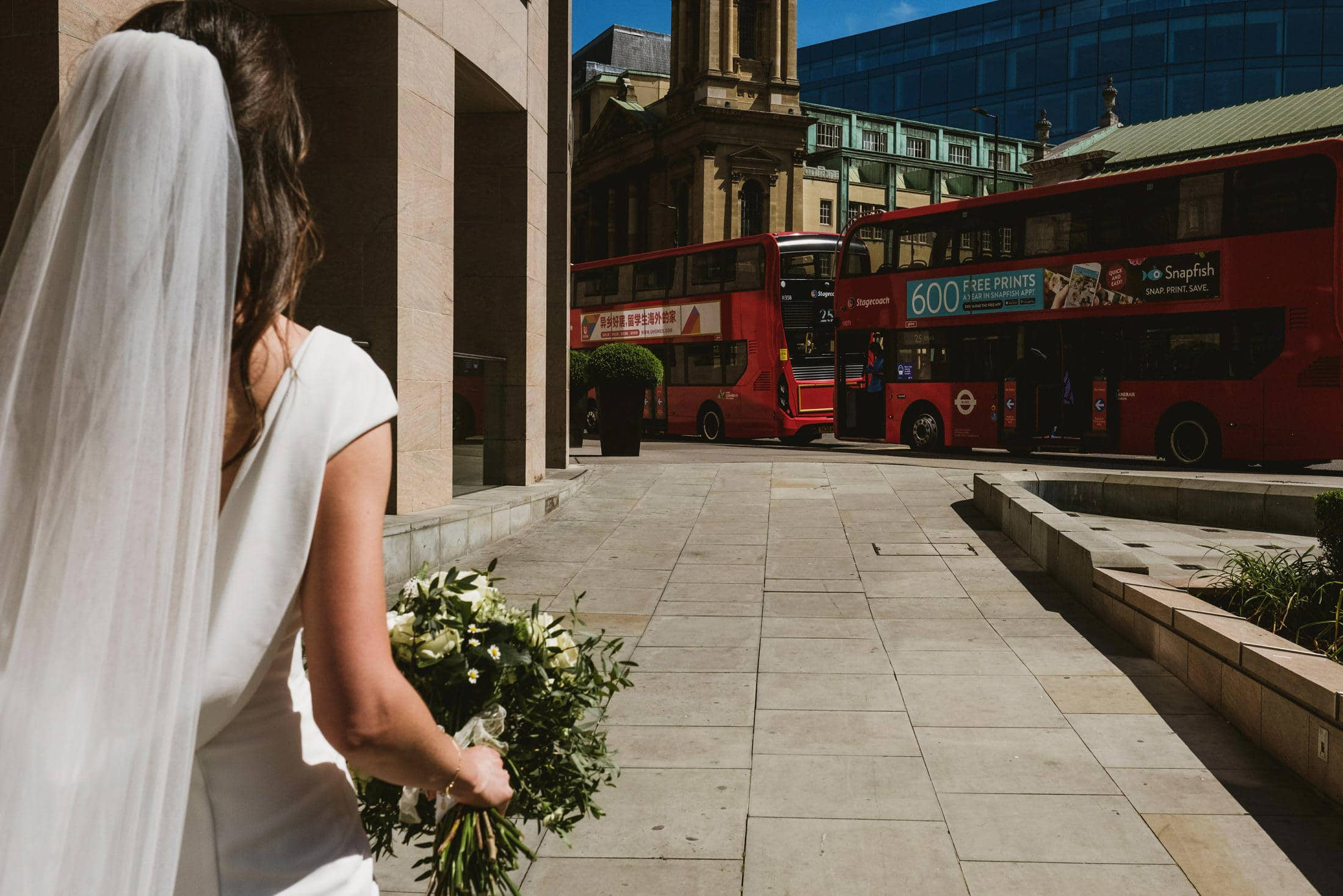 A bride walks down the street away from camera towards some London double-decker red buses. In her hand is her bouquet.