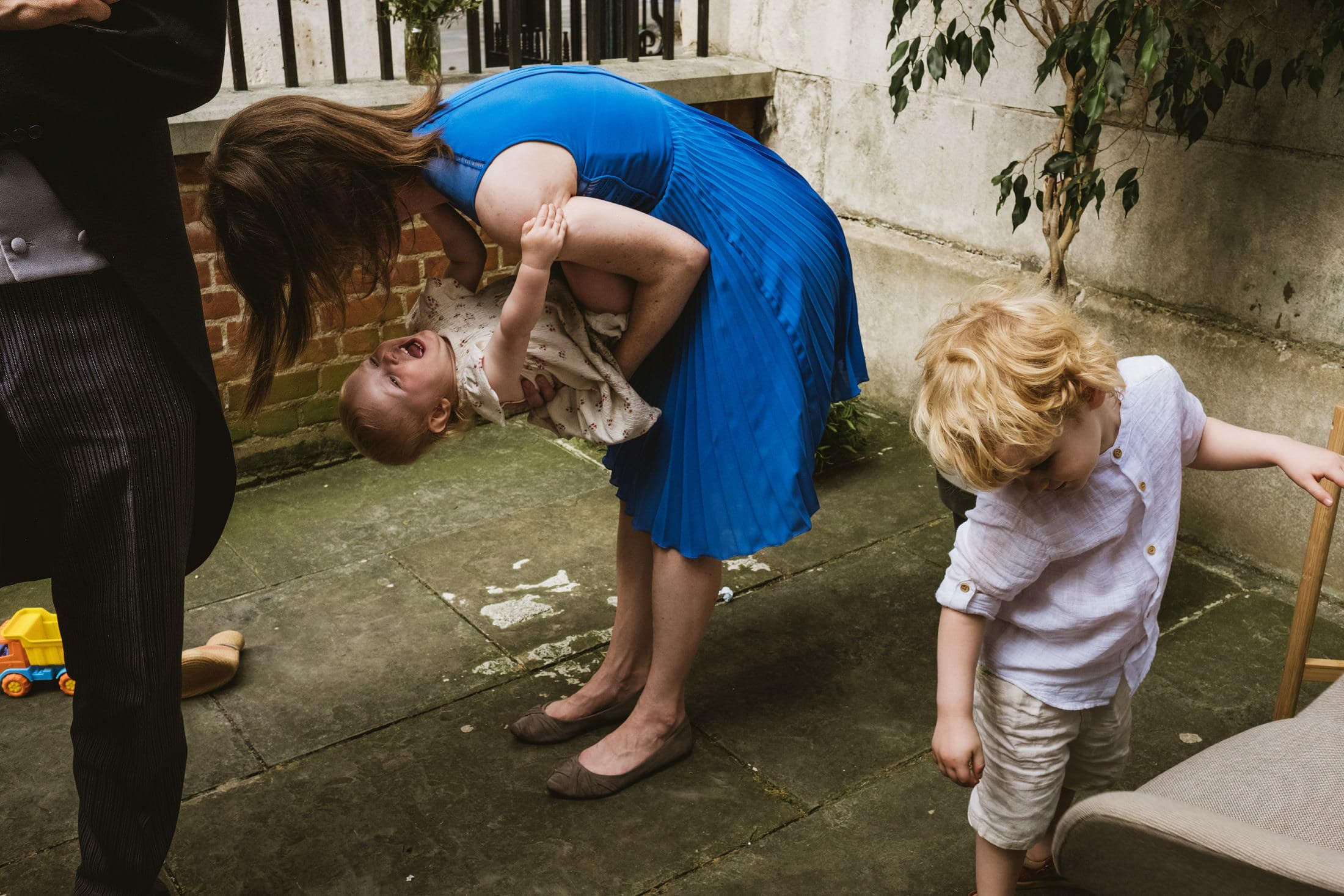 Woman in blue dress bends over and plays with the baby she is carrying at a London outdoor wedding reception. Right of the frame another child stands looking down at the floor inquisitively whilst on the left of the frame we can see a mans legs in pin-striped trousers