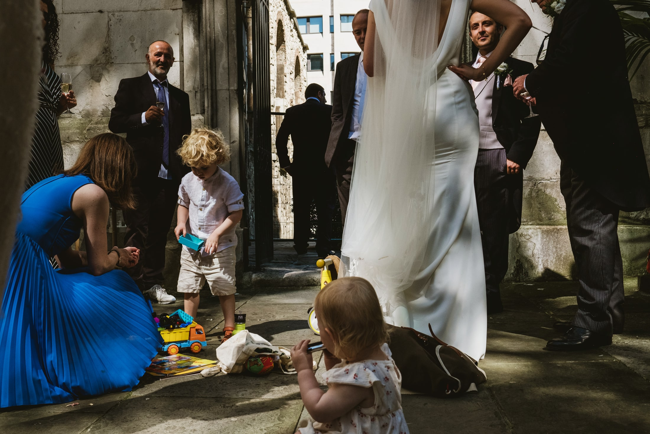 Multiple small stories erupt between the guests and children at an outdoor London wedding ceremony. The photograph is carefully framed to allow each story room to breathe and embrace the light and shadow of the area.