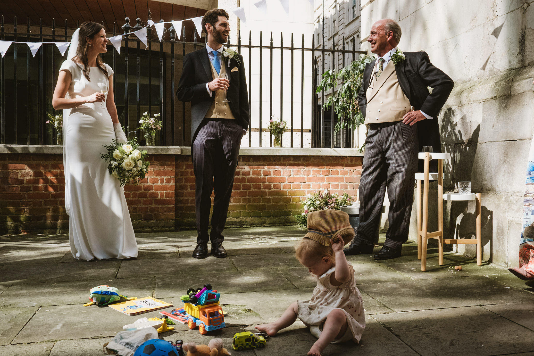 A young child seated outside on the ground front centre plays with a hat. Around her are lots of children's toys. Behind her the father of the bride speech is under way. Standing behind her the bride, groom, and father of the bride hold champagne glasses and laugh