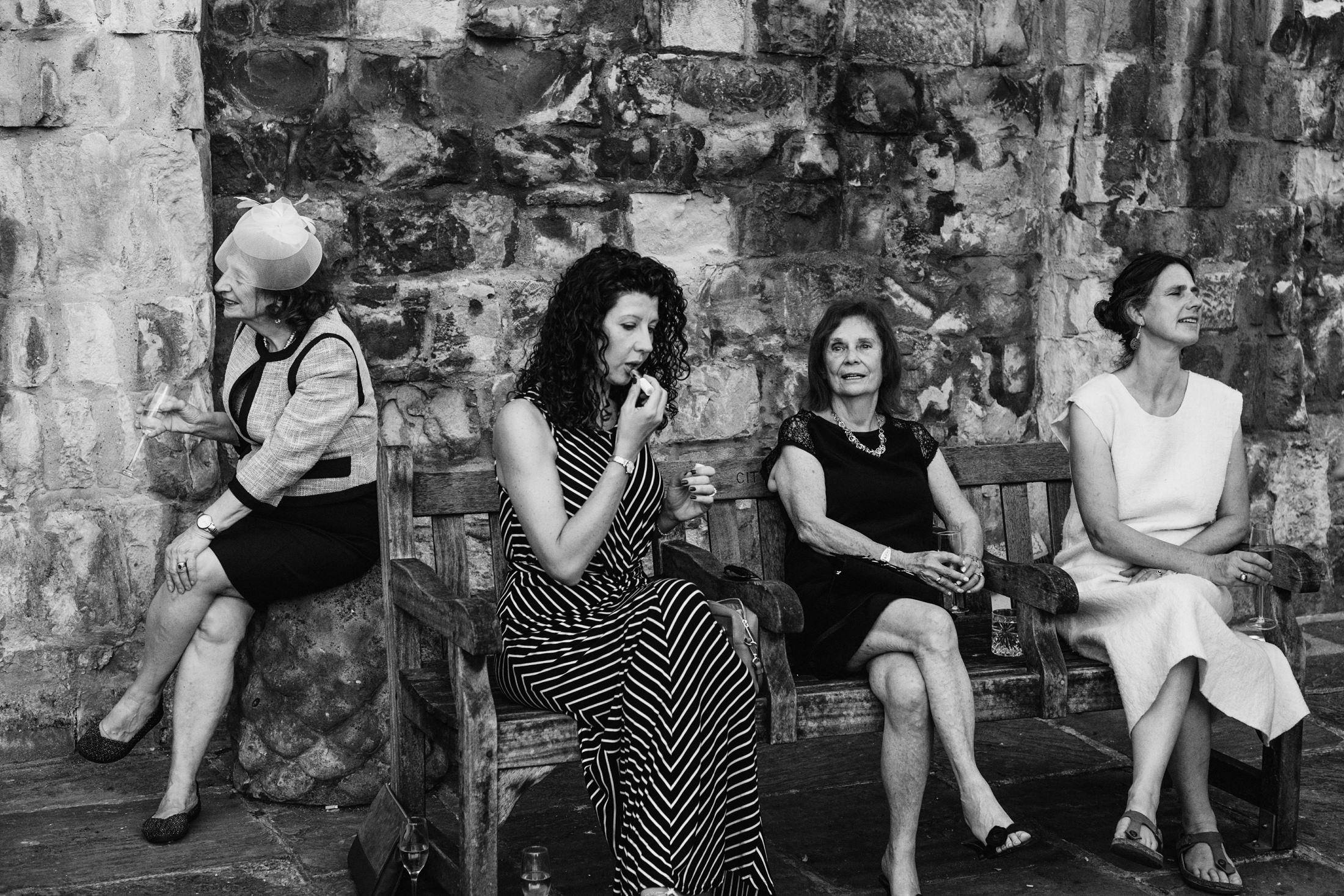 Intimate black & white documentary wedding photograph of guests sitting on a bench at a micro wedding reception. Though they are seated together each is engaged in entirely separate mini-stories from one another