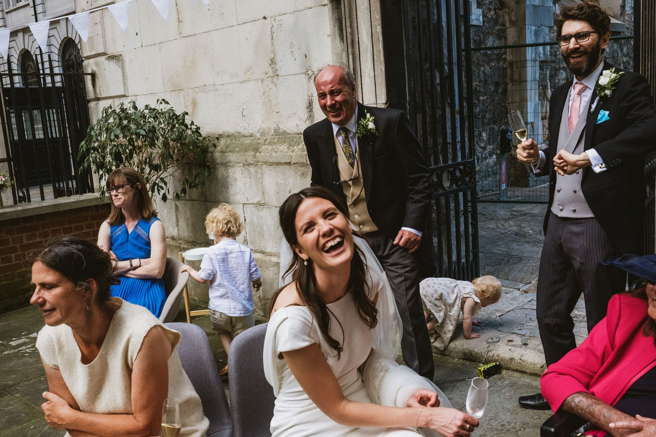 Bride (front, centre) laughs hard at a joke also enjoyed by her father standing behind her and a groomsman to her left. Between and around them multiple other stories are evolving, including a child crawling out through the gates behind