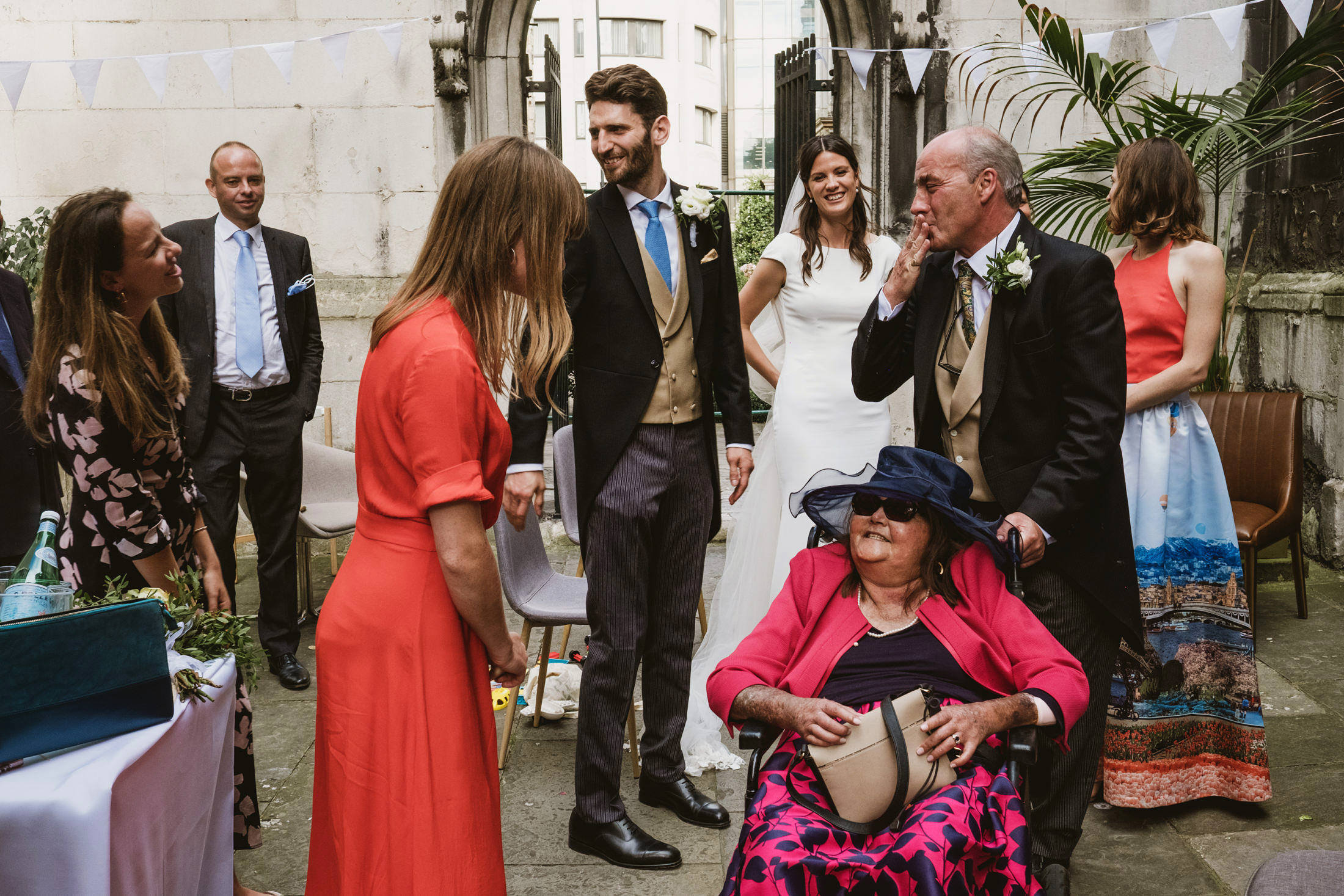 Multi-layered street documentary wedding photograph at an intimate London wedding reception. Bride and groom stand centre, to their right is a woman in a wheelchair, being pushed by the father of the bride who blows a kiss to one of the guests. Several other guests watch on.