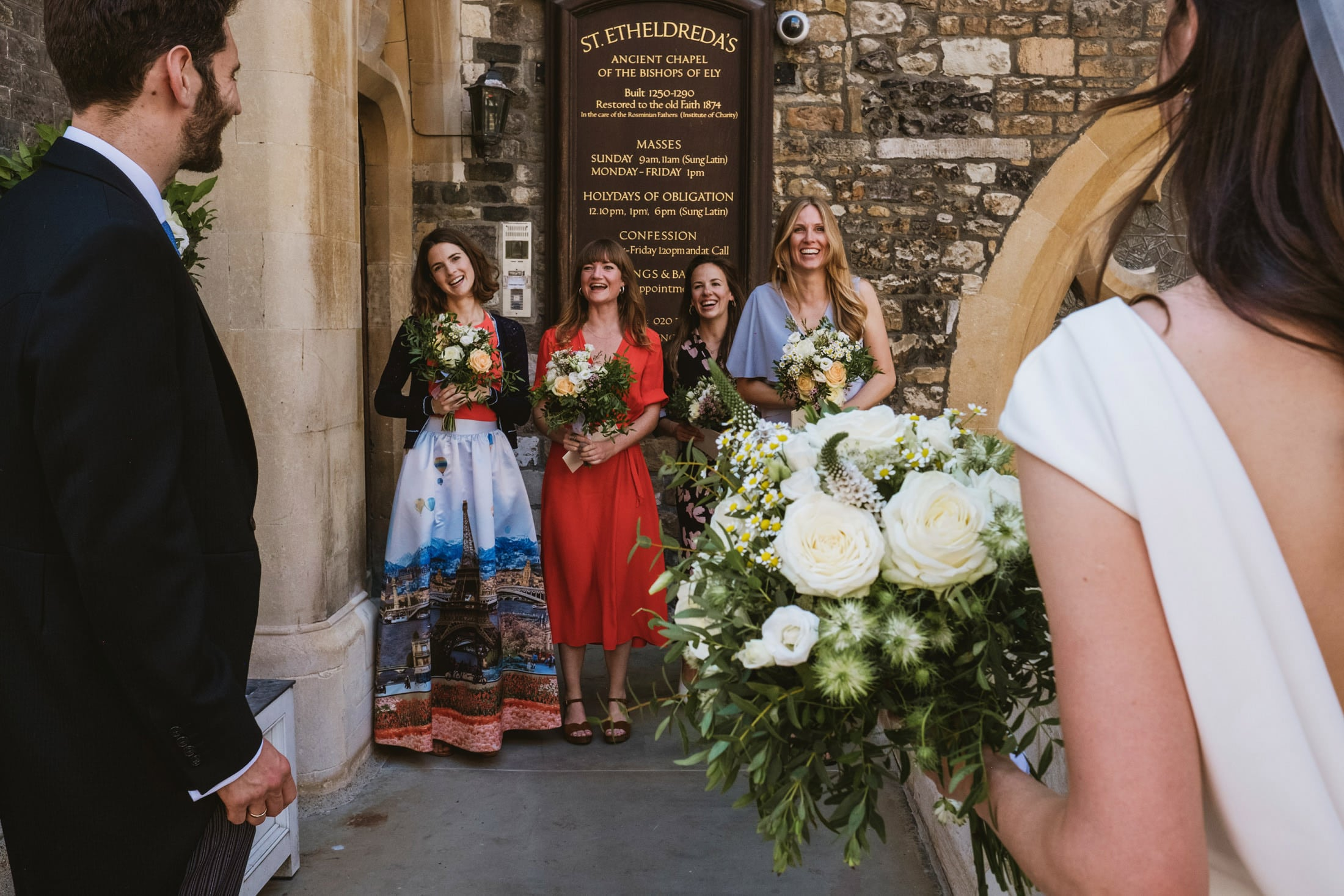 Right of the frame we see the shoulder of a bride holding her bouquet. To her left is her groom. Both look back towards the four bridesmaids smiling at them and framed between them. Intimate London wedding photography outside St Etheldreda's Church