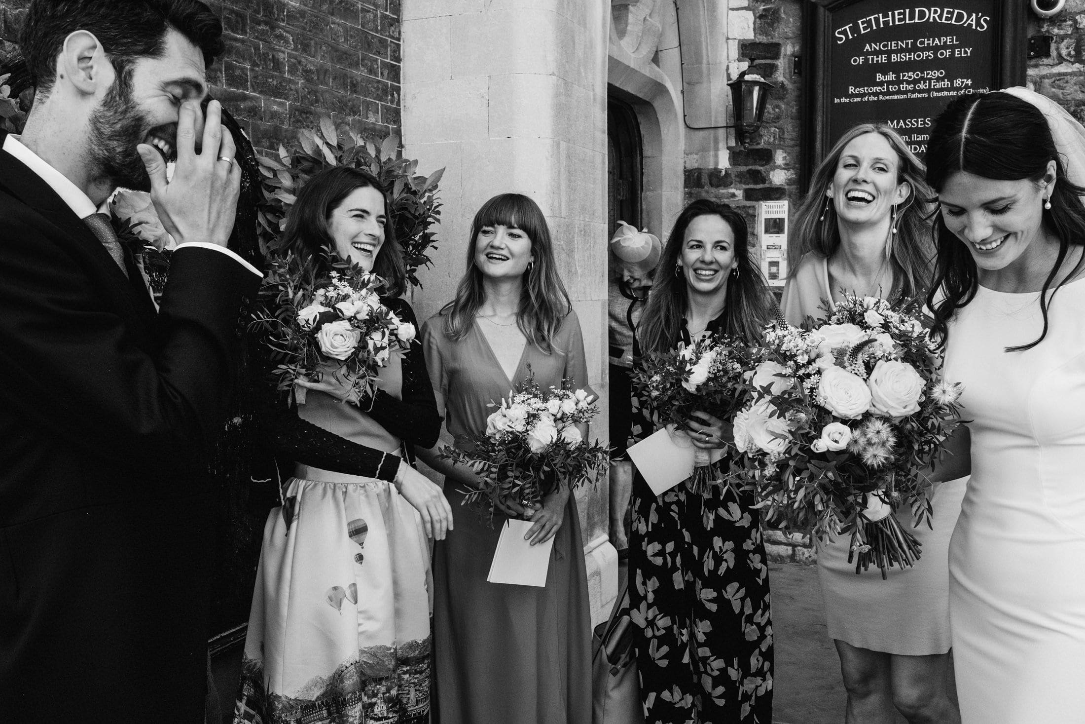 Black & white documentary wedding photograph outside St Etheldreda's church in Londona laughing bride and groom stand either side of the frame, between them four female guests enjoy the joke, another guest framed between them