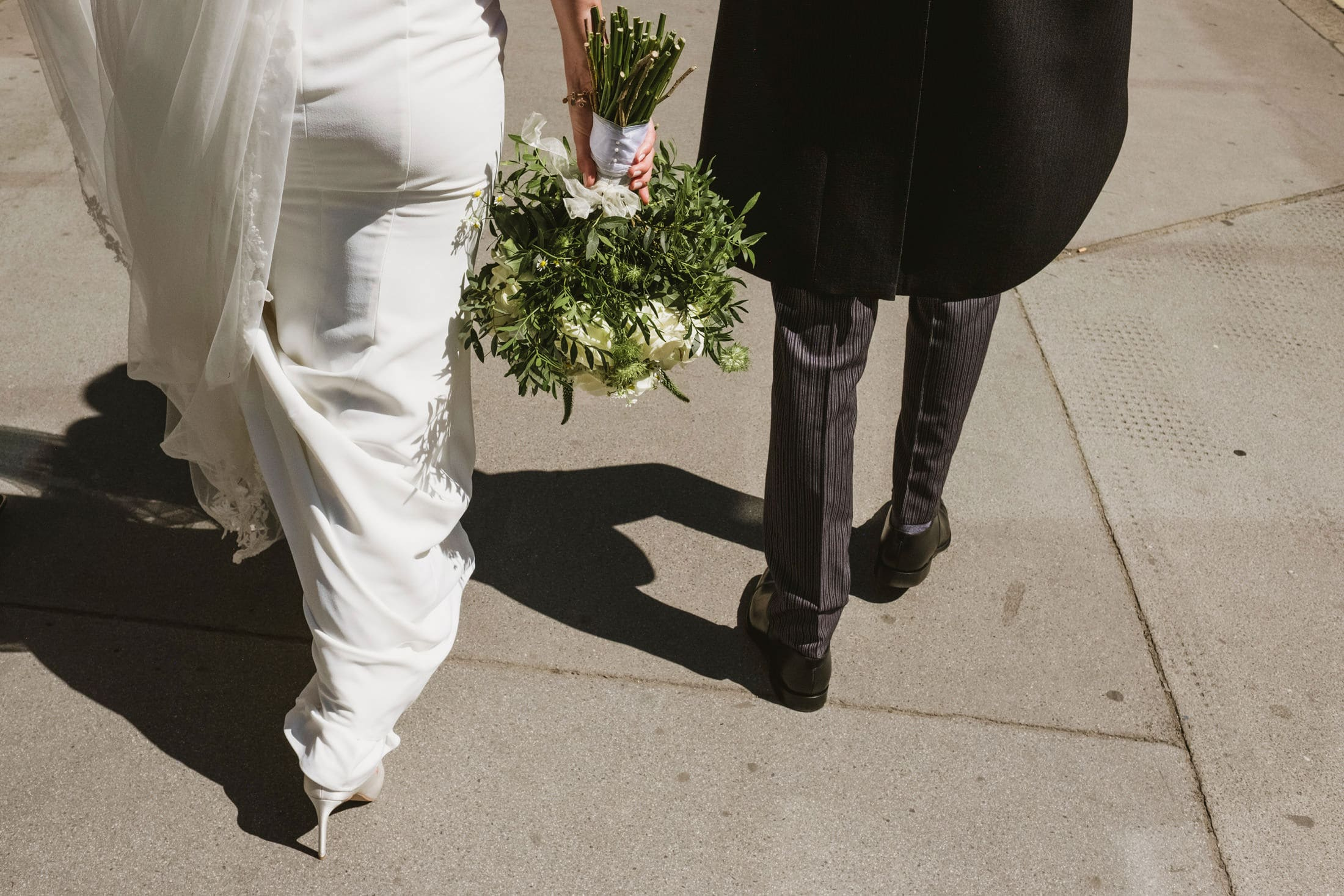 Street style documentary wedding photograph captured in London. A bride and groom's legs photographed from behind as they walk down a London street. Between them the bride holds her bouquet upside down.