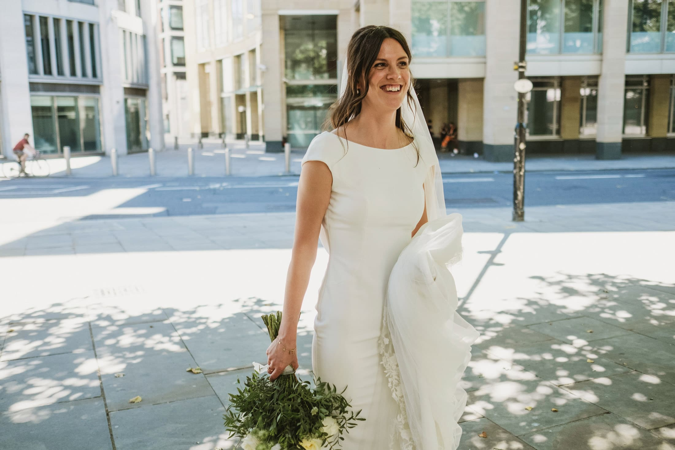 Bride walks through the London streets holding her bouquet by her side casually. Street documentary wedding photography by Dominique Shaw