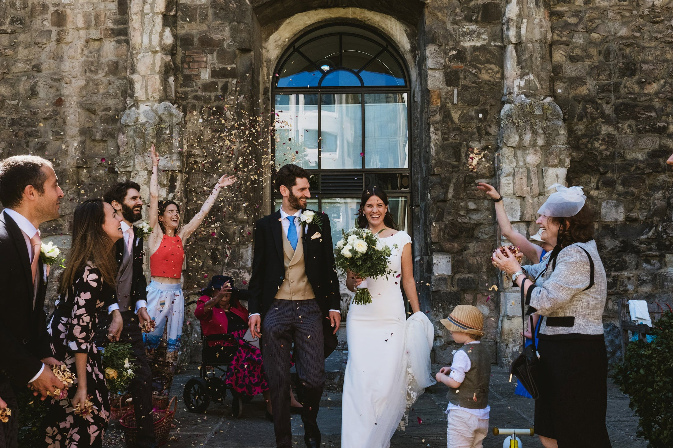 Bride and groom are showered in confetti by their guests at a small London wedding