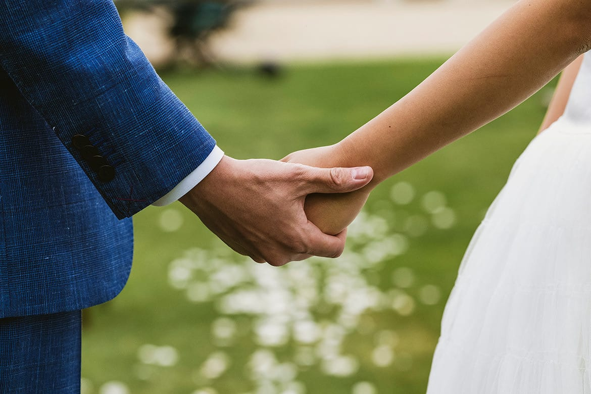 Film scene from a micro wedding video in York. Close in of a bride and groom holding hands as they stand on a lawn during a micro wedding ceremony