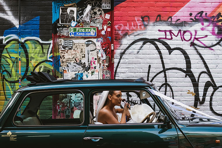 Small, intimate wedding in London. Side view of a green mini fitted with white wedding ribbons and parked in front of a wall covered in graffiti. In the front seat a bride can be seen touching up her makeup