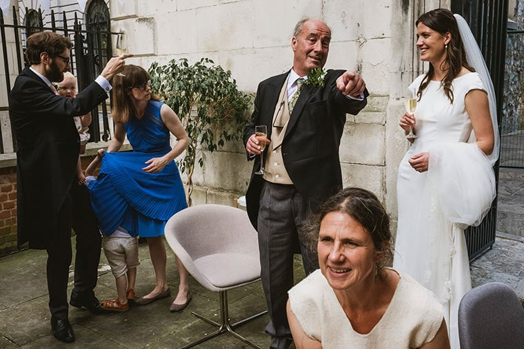 Small intimate wedding taking place in London. Front right a seated guest looks across the frame. Behind her and to the right the bride and her father converse, the father pointing diagonally across the frame. Rear left a man in a suit points towards the centre rear of the frame whilst holding a child in his other arm. Next to him a woman stands, another child playing with her dress and mostly hidden amongst the folds.