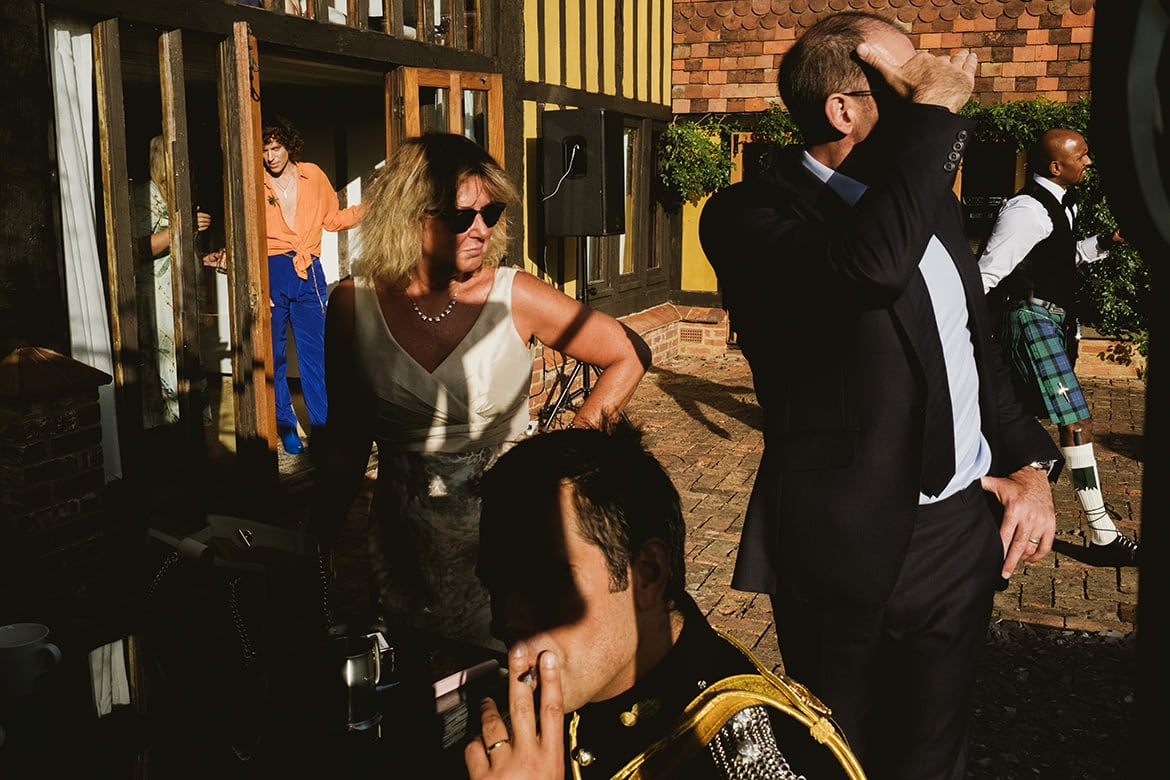 Micro wedding scene in the courtyard of a couple's home in Kent. At the front centre of the frame the groom (in full military dress uniform) is seated smoking a cigarette, his face in partial shadow. Behind and to the left a woman in sunglasses and a white dress looks to her left. Right of her a man in a suit covers his eyes with his hands. Framed to his right a man in a kilt is walking towards the edge of the frame. Far left a man in extravagant dress is framed in the doorway of the Tudor style house.