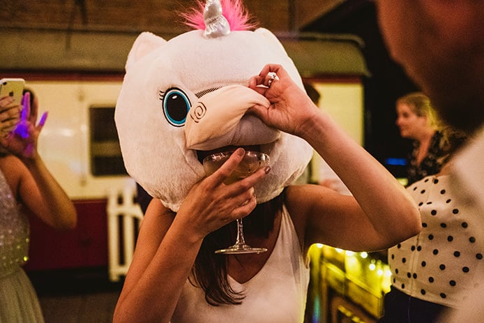 Newcastle Wedding photography by York Place - Bride wearing the head of a unicorn costume tries to take a drink of wine on the wedding dancefloor