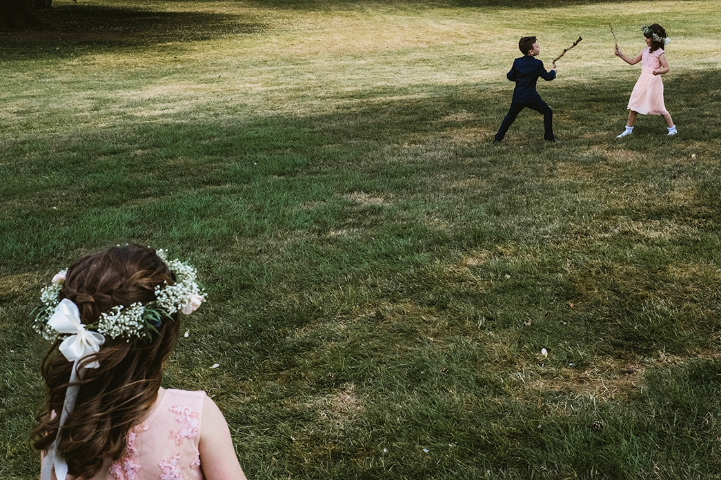 children at wedding reception have a sword fight whilst another flower girl watches on. Photographed in a reportage style