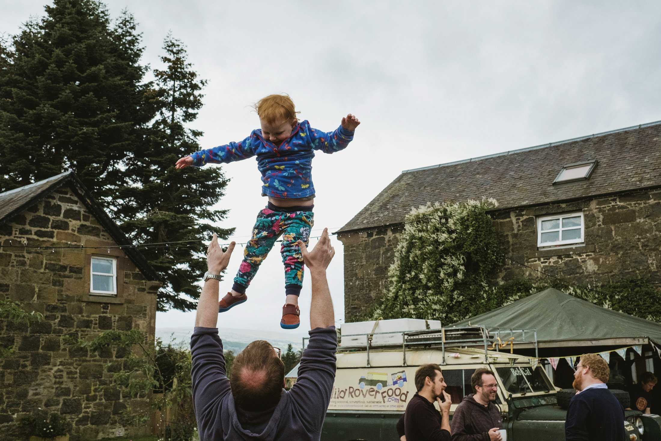 Reportage wedding photography at Comrie Croft, Scotland. Child thrown into the air (playfully) by a parent
