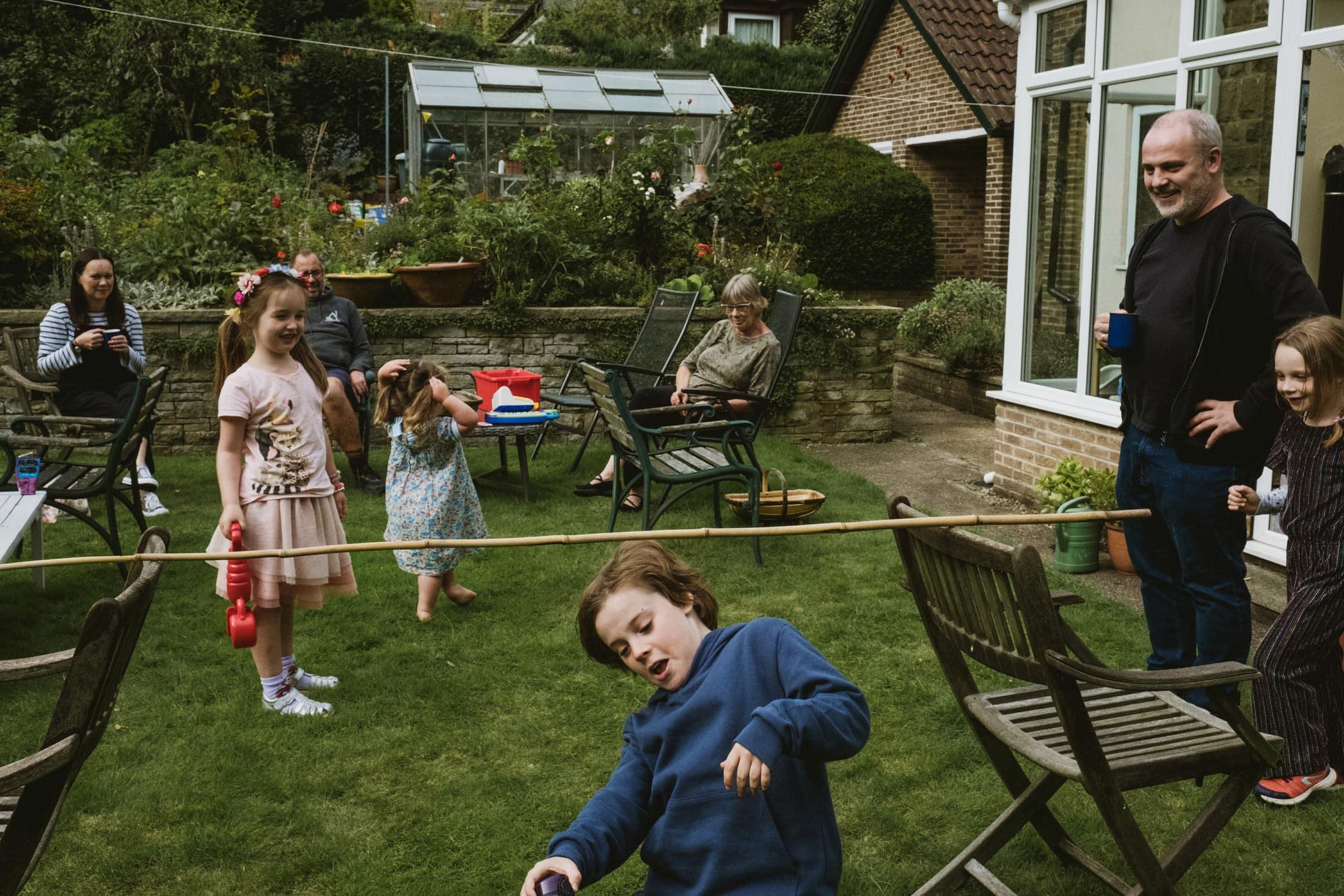 playing limbo with make shift stick. Boy underneath limbo stick, family watching