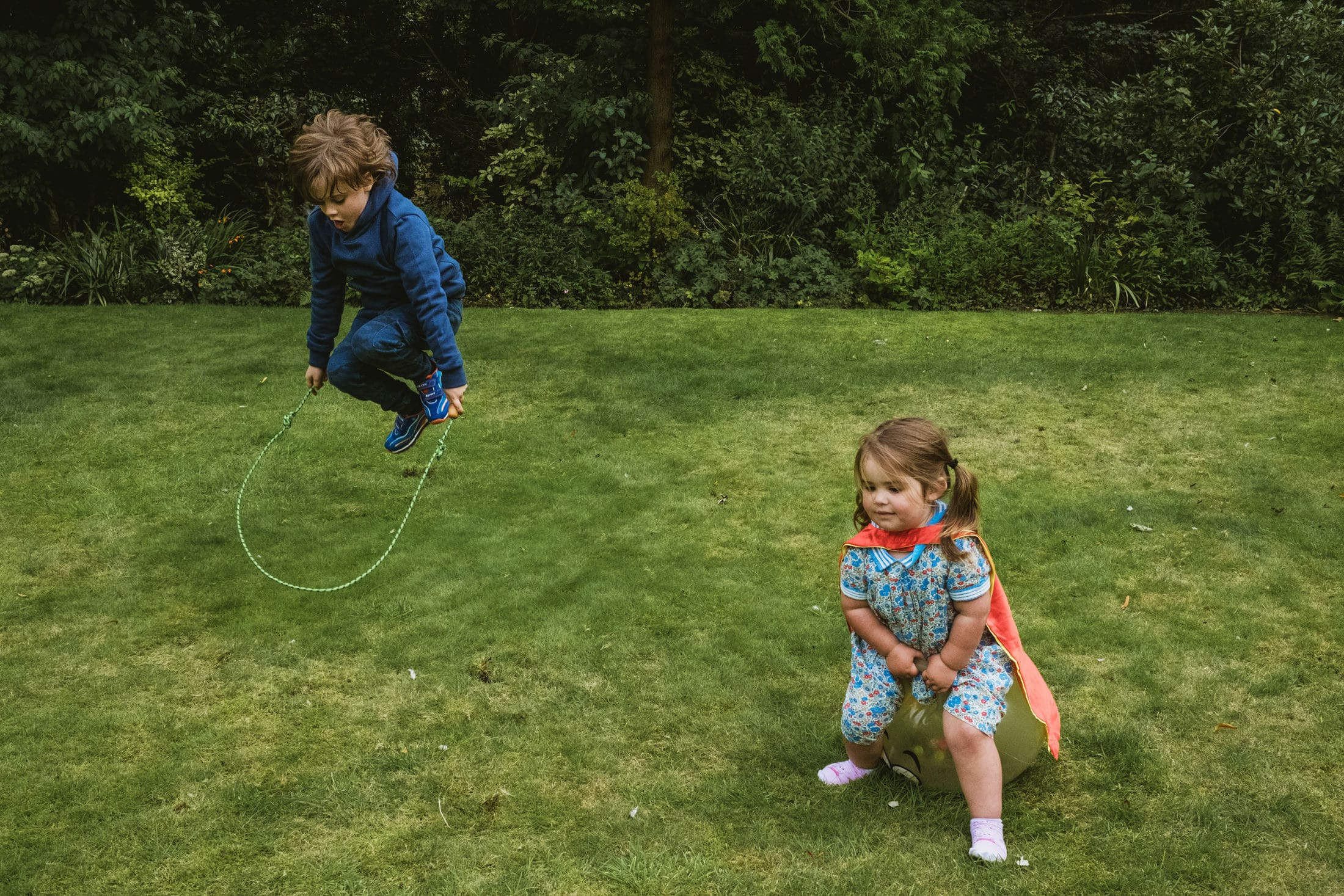 Documentary family shoot, boy jumping with skipping rope, little girl on bouncer wearing a superhero cape