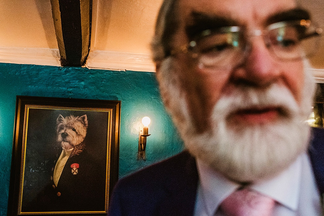street style wedding image - man at wedding stands on right of frame, to his left is a portrait of a dog in a suit who humorously shares similar facial features.