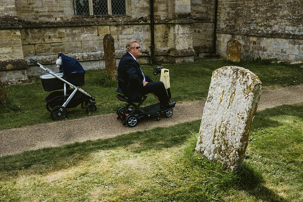 street style wedding image representing the journey of life - pram on left of frame, man on disability scooter in centre and gravestone to the right of the frame.