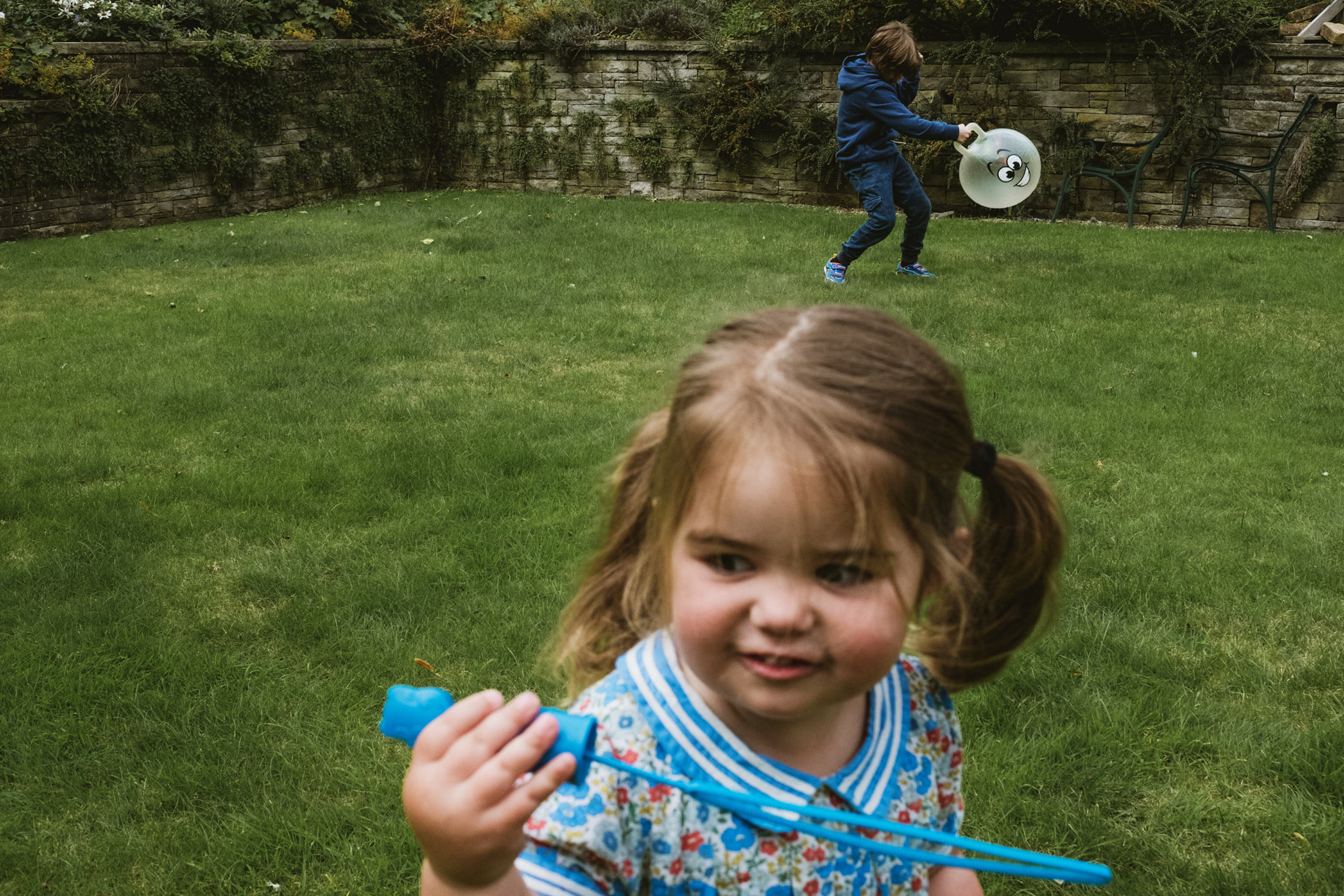 little girl blowing bubbles, young boy playing with bouncer. Documentary family photography