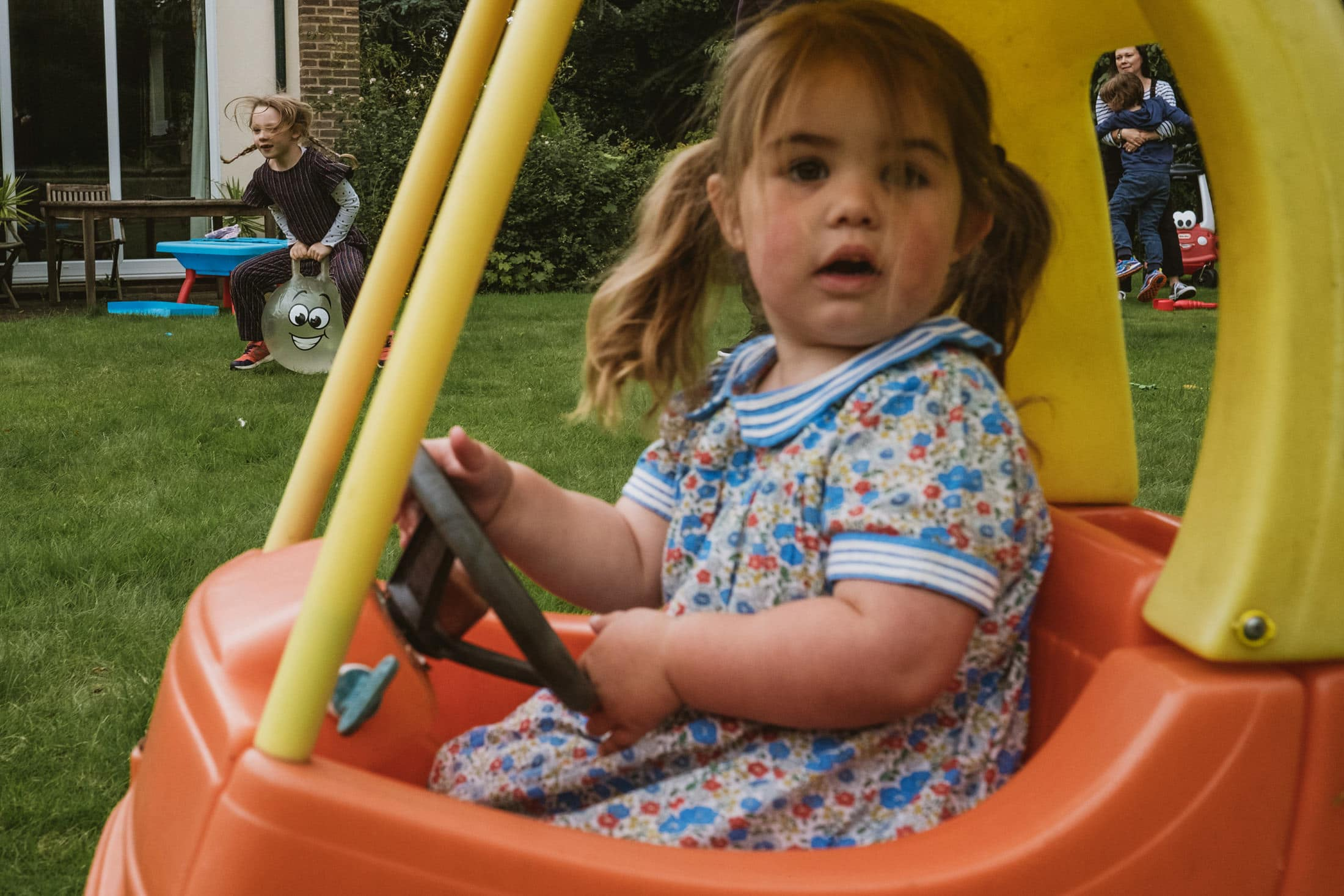 little girl in toy car and other children in the background. Documentary family photography